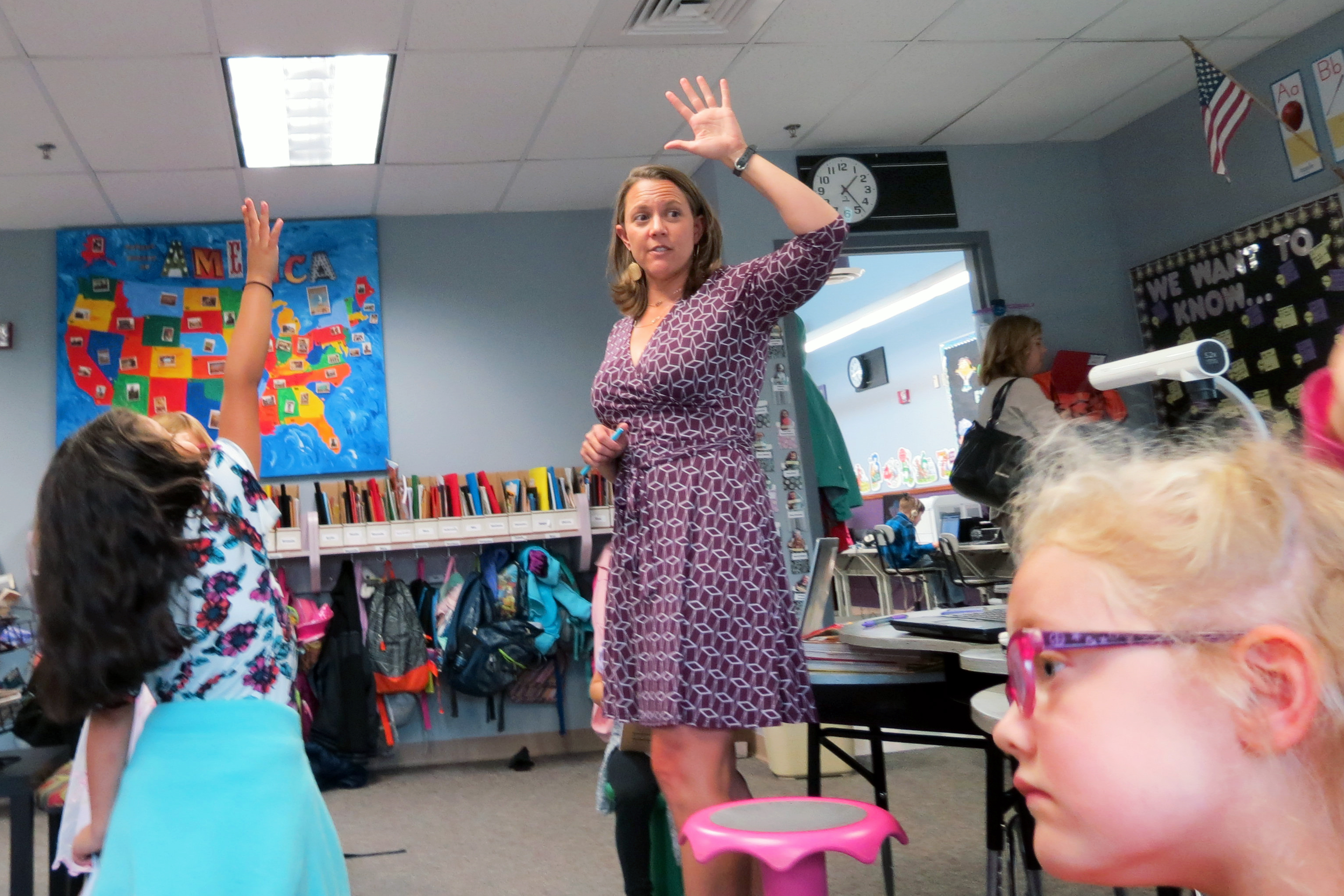 <p>Kindergarten-First grade teacher Kaylee Vasquez (with hand in air) asks her students to come up with five questions they want to answer about their projects. Some questions students have chosen: how a computer works, why each state has its own flower, and why your stomach feels weird when you fly.</p>