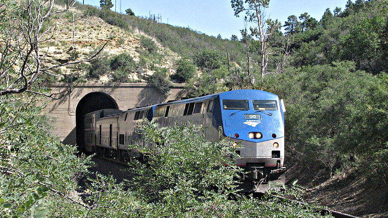 """<p><span style=""""font-family: sans-serif;font-size: 13px;line-height: 16.714229583740234px"""">Amtrak engine 99 pulls the westbound Southwest Chief out of the Raton Tunnel near the summit of Raton Pass.</span></p>"""
