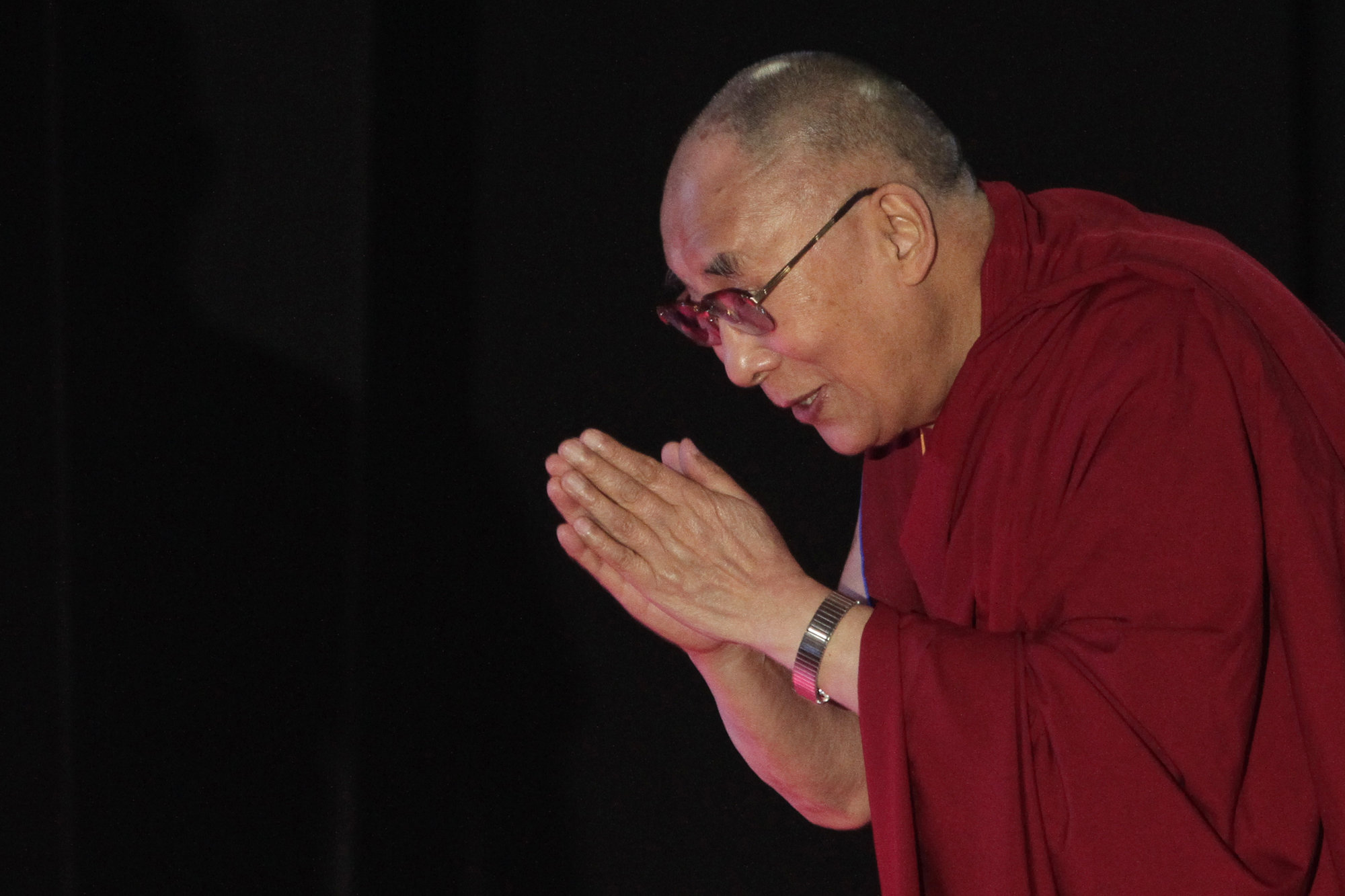 """<p>Tibetan spiritual leader the Dalai Lama greets the audience as he arrives to speak on """"A Human Approach to World Peace"""" at Presidency College in Kolkata, India, onJan. 13, 2015.</p>"""