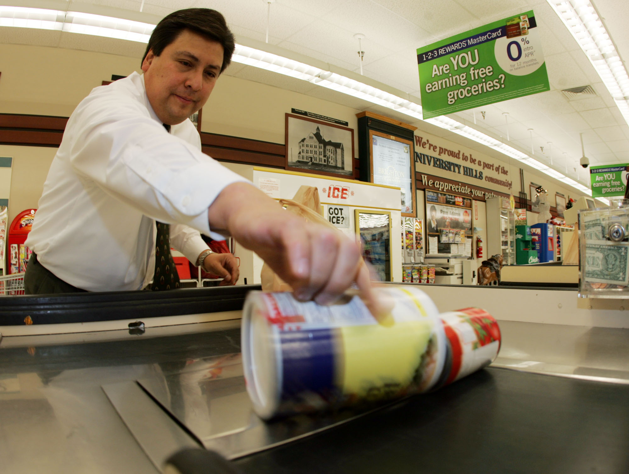 <p>Les Gomez, store manager of a King Soopers in southeast Denver, grabs an item off the converyor belt as he bags groceries for a customer in a file photo.</p>