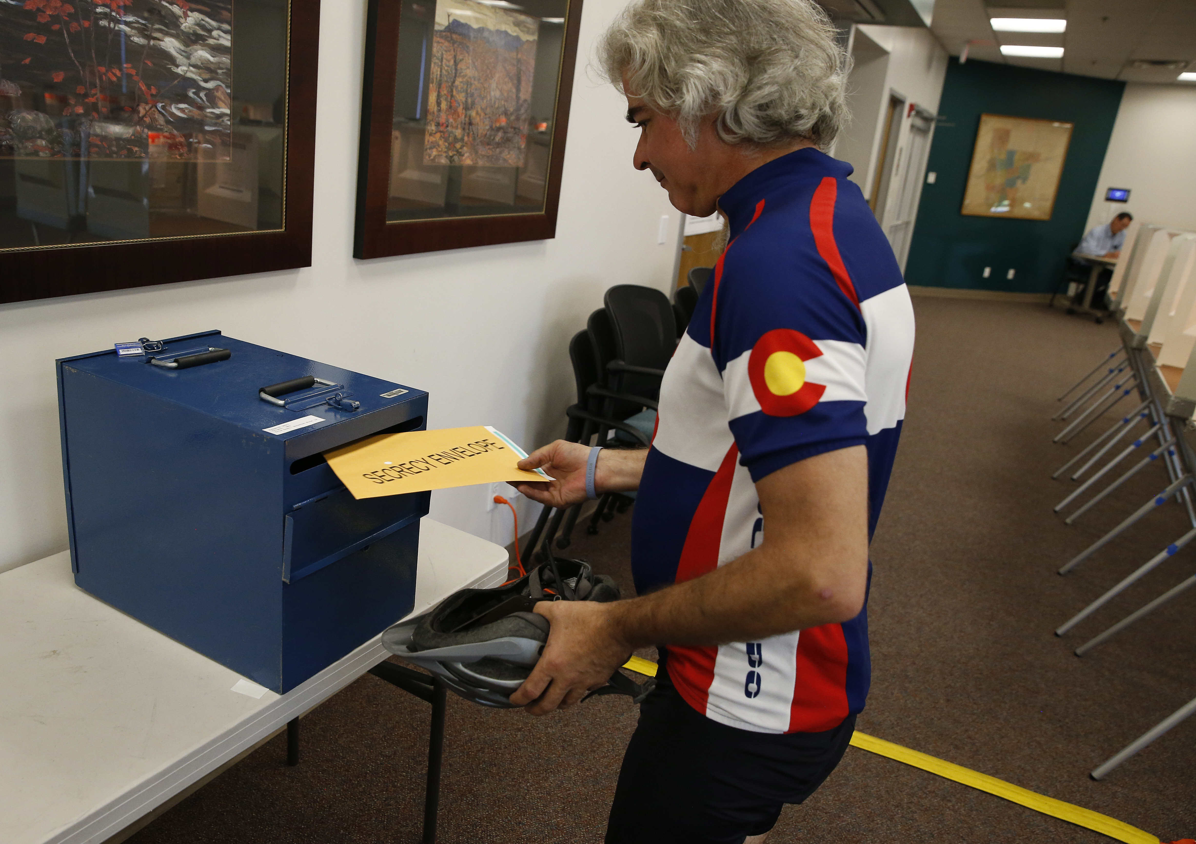 <p>A voter places his ballot into a collection box after filling it in at a polling center, on state primary election day, in Boulder, Colo., Tuesday, June 28, 2016.</p>