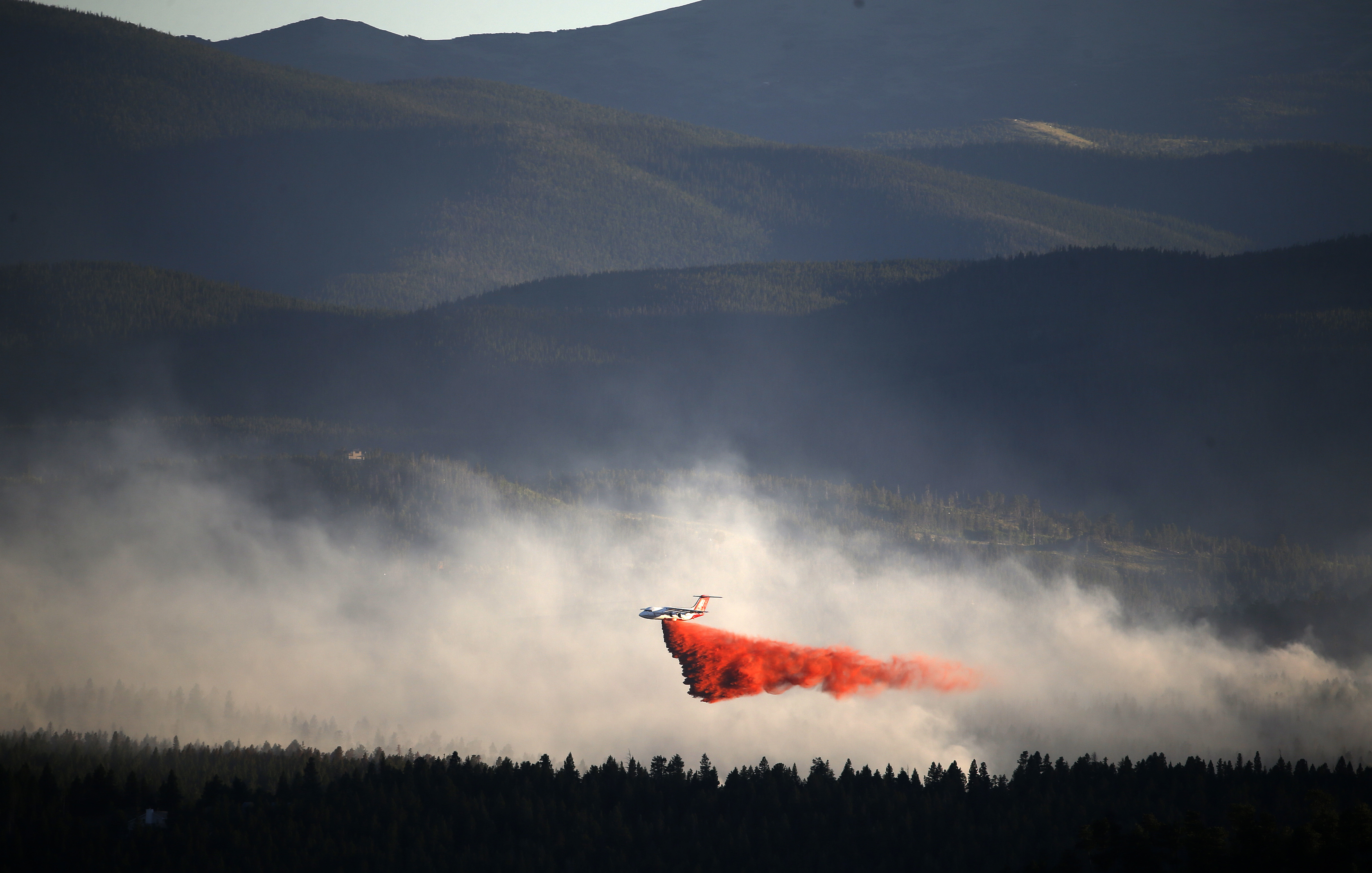 <p>A plane drops retardant while battling the Cold Springs Fire near Nederland, as viewed from Sugarloaf, Colo., Sunday, July 10, 2016.</p>