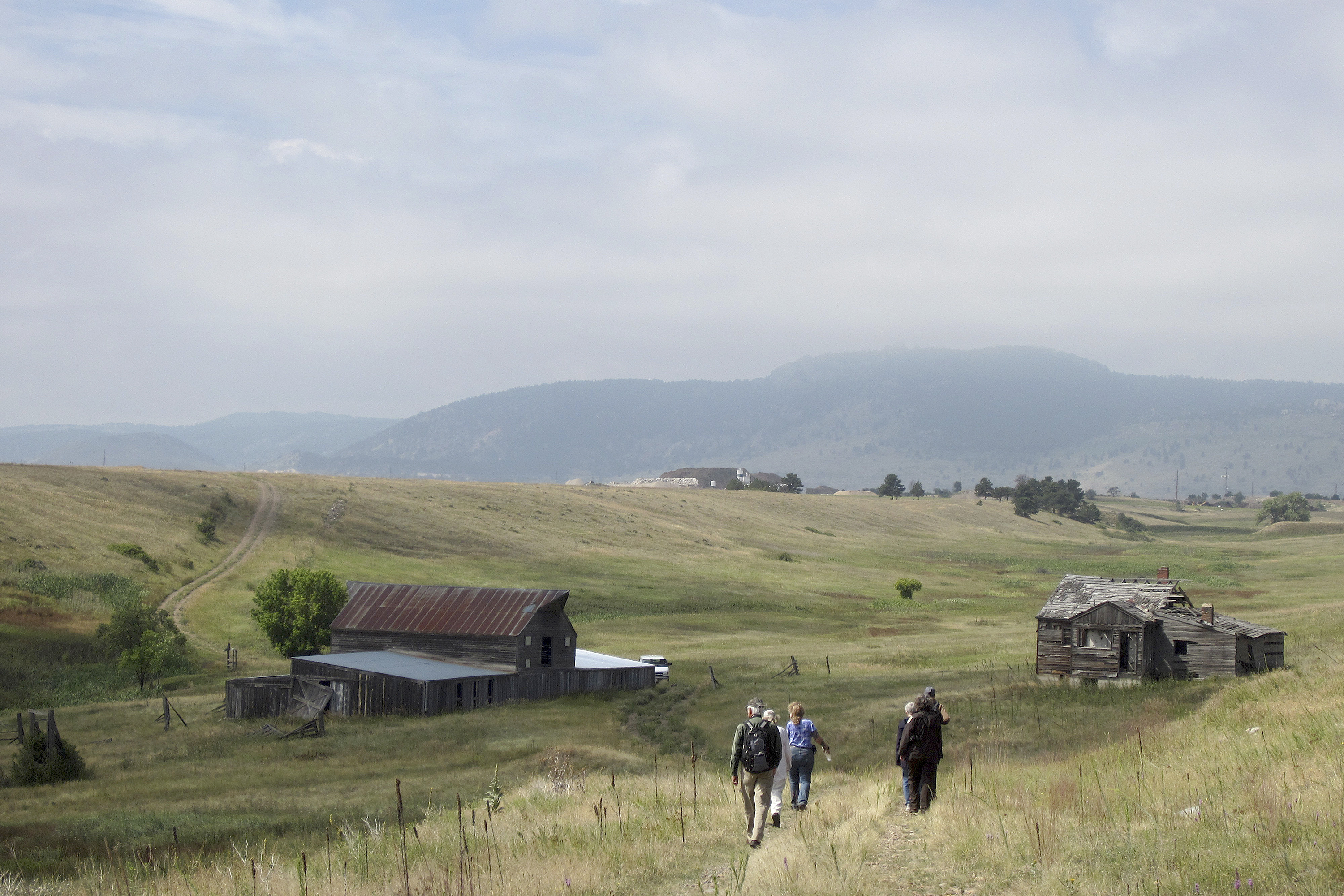 Visitors approach a former ranch house and barn during a guided hike on the Rocky Flats National Wildlife Refuge near Denver.