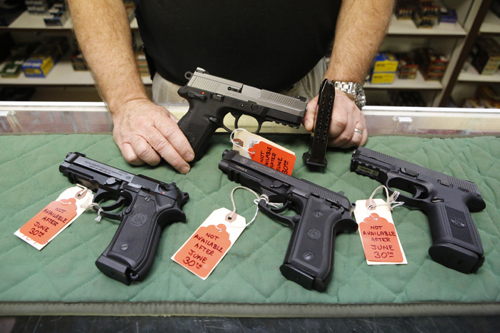 <p>In thisJune 2013file photo, Richard Taylor, manager of Firing-Line gun store in Aurora, Colo., shows pistols for sale.</p>