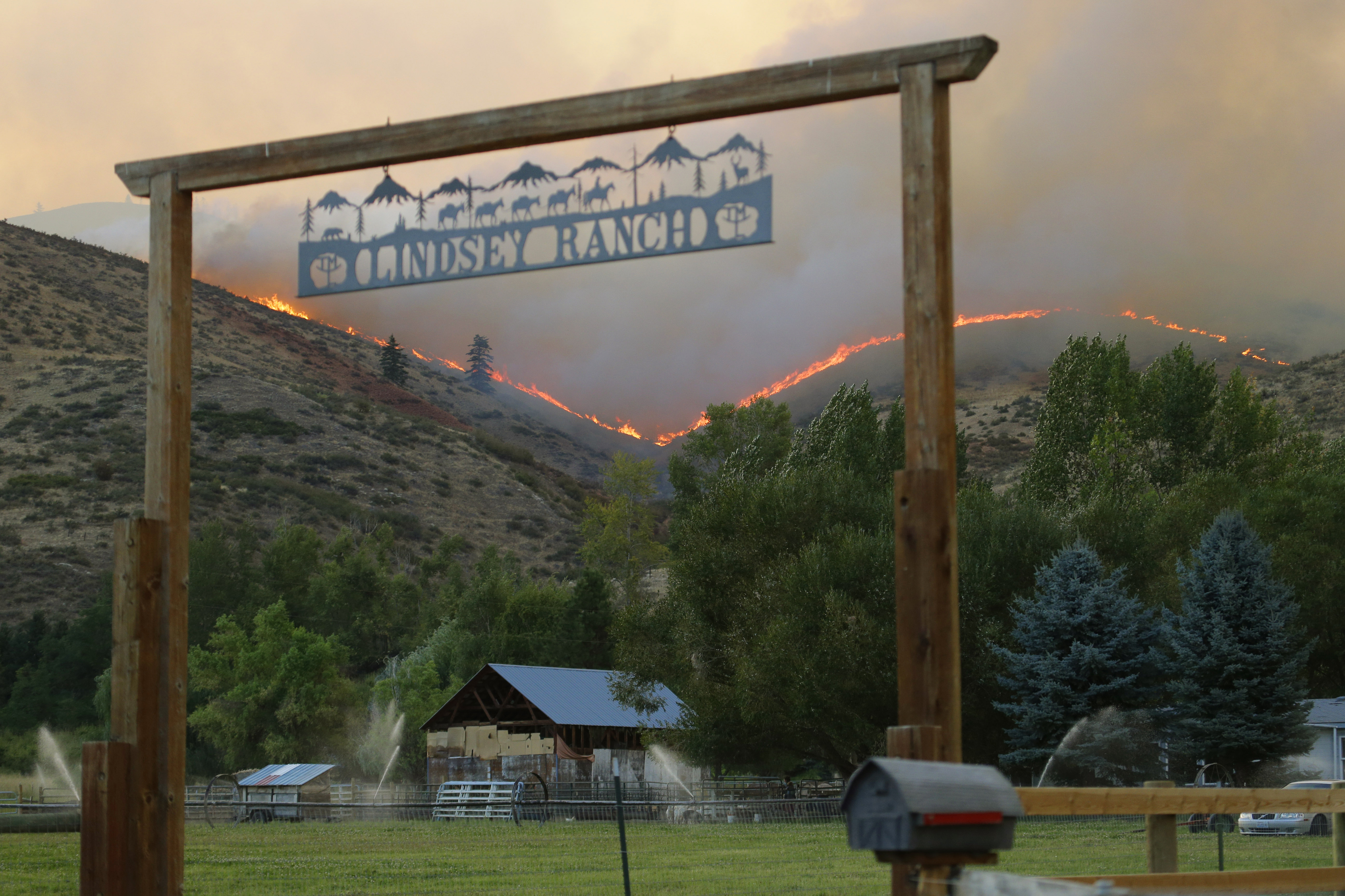 <p>Flames and smoke rise on a ridge line above a ranchin Twisp, Wash., Wednesday, Aug. 19, 2015.</p>