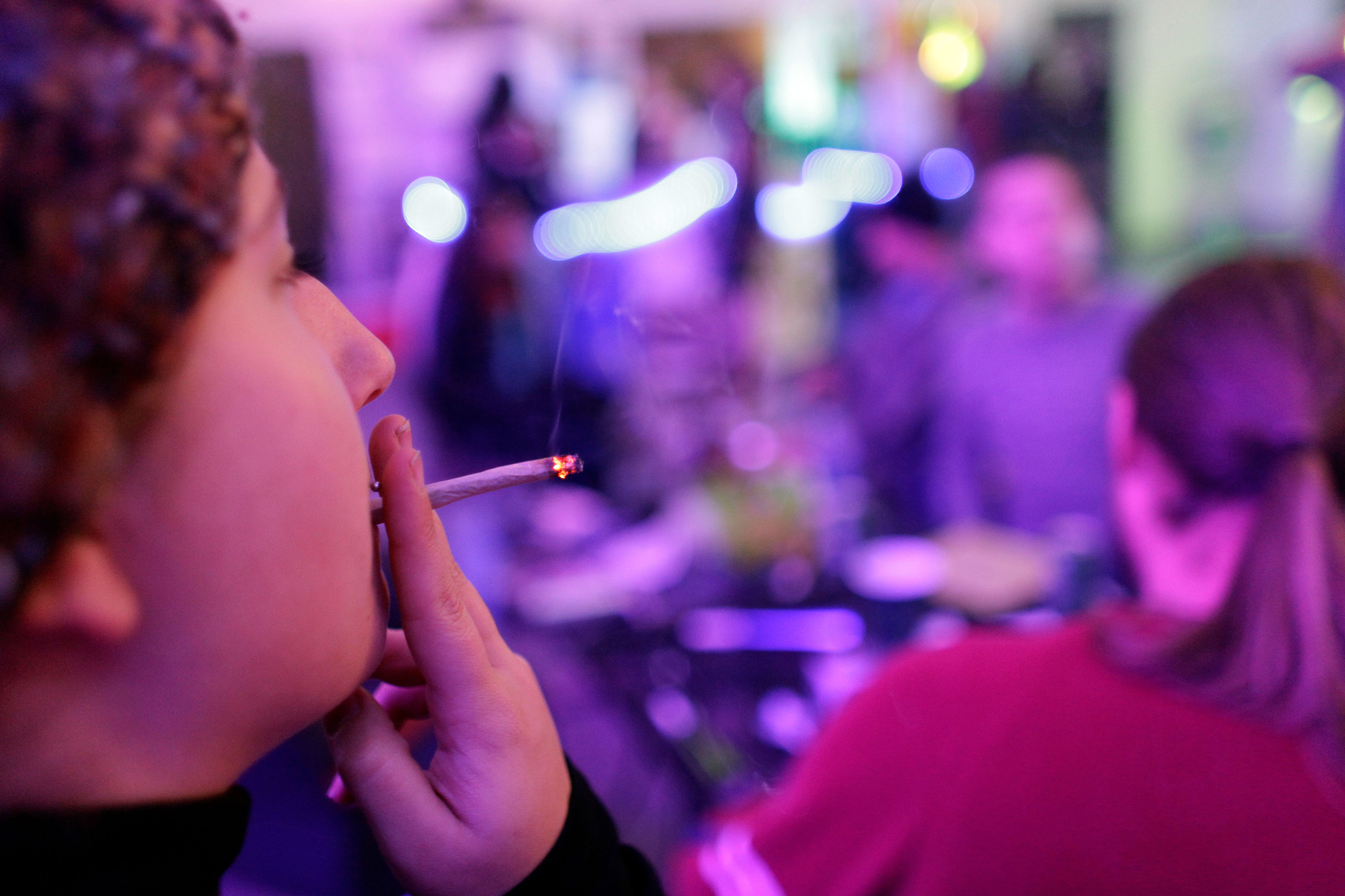 <p>Grace Sisti, of Denver, smokes a joint on the official opening night of a marijuana-specific social club, Monday Dec. 31, 2012.</p>