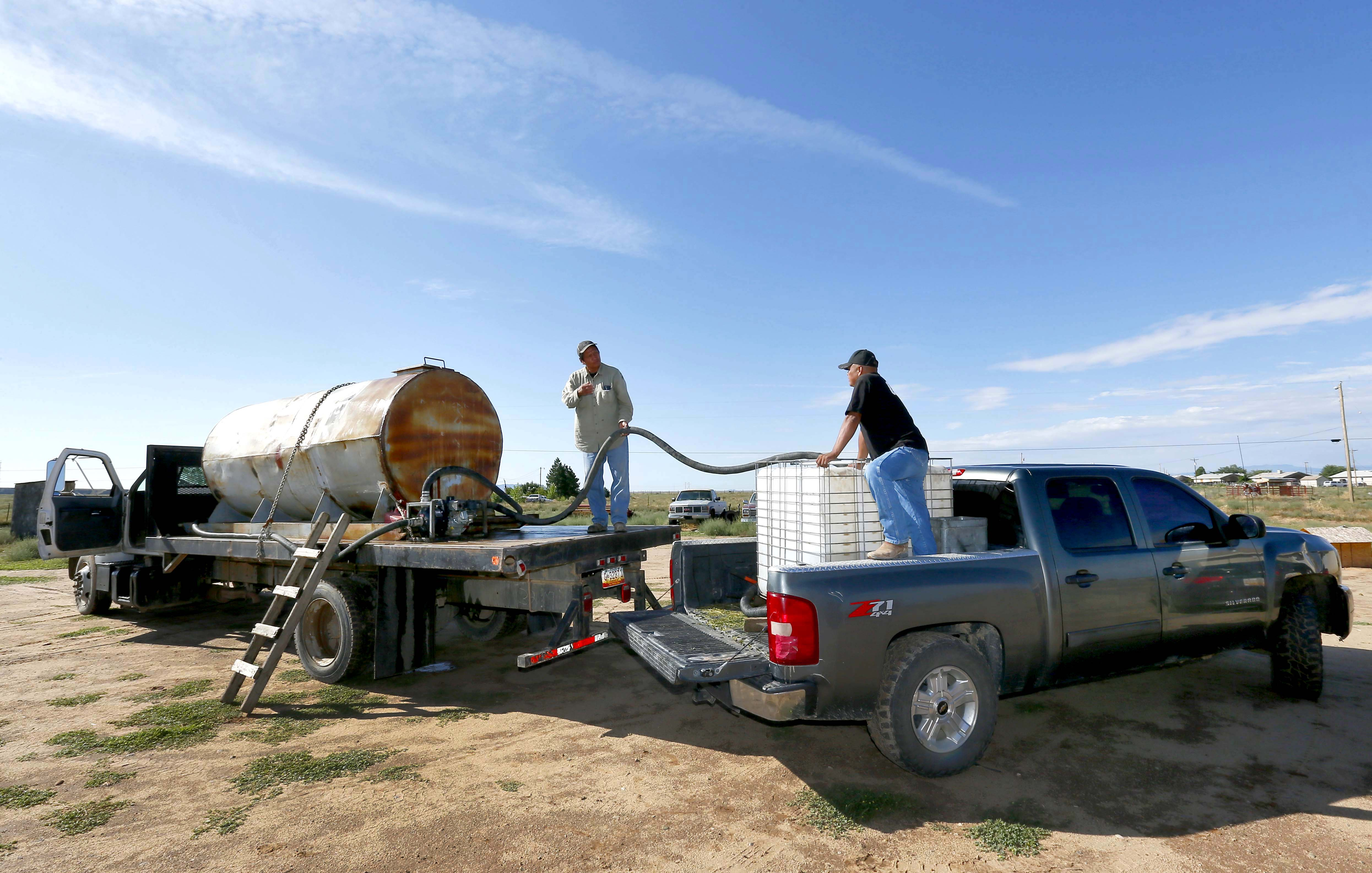 <p>Melvin Jones, left, delivers water to rancher Timothy Curley along the San Juan River on the Navajo Reservation, Wednesday, Aug. 12, 2015, in Shiprock, New Mexico.</p>