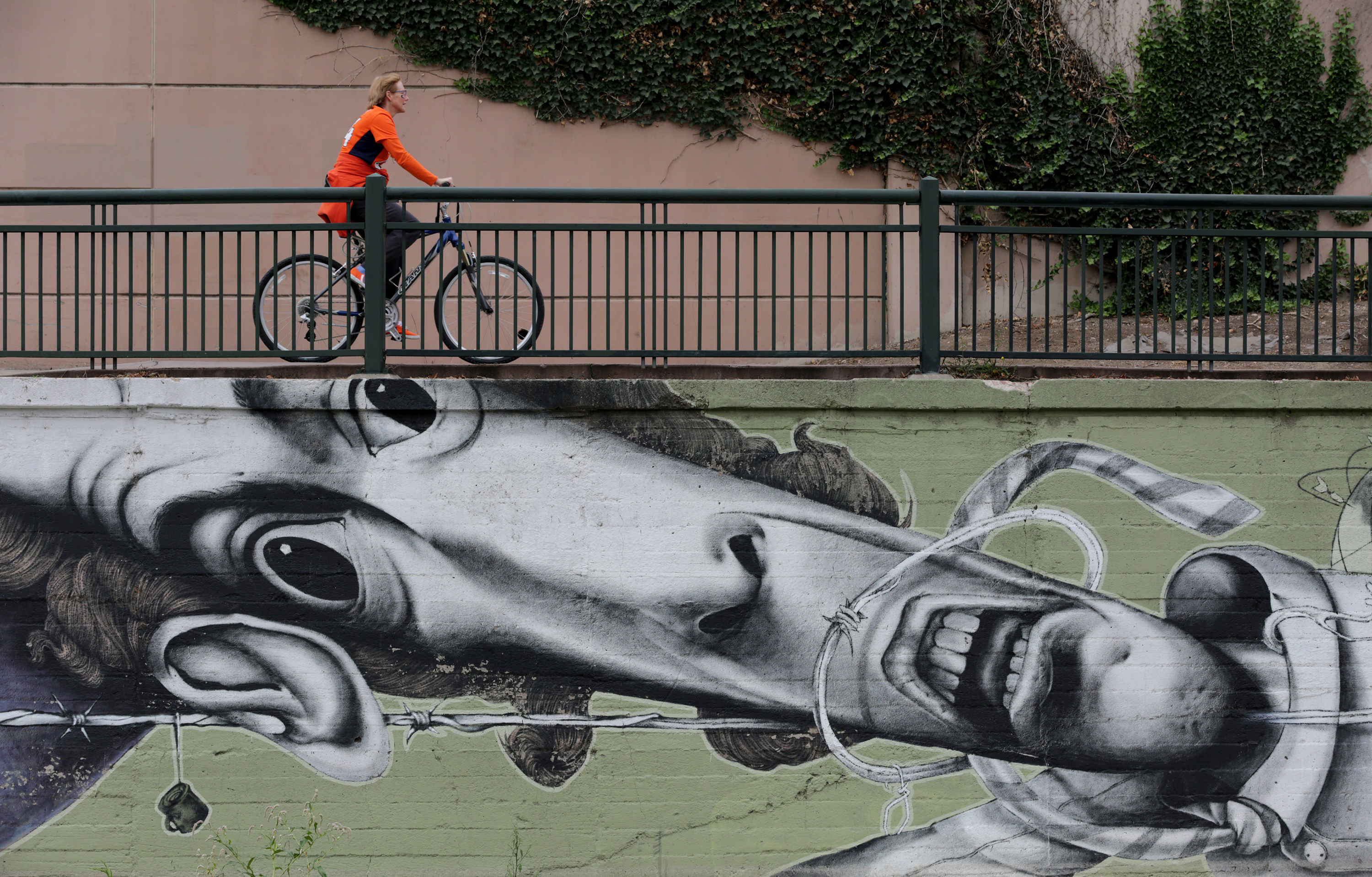 <p>A cyclist rides on the Cherry Creek bike path above a graffiti mural commissioned by the city of Denver near Confluence Park on Sunday, Oct. 4, 2015.</p>
