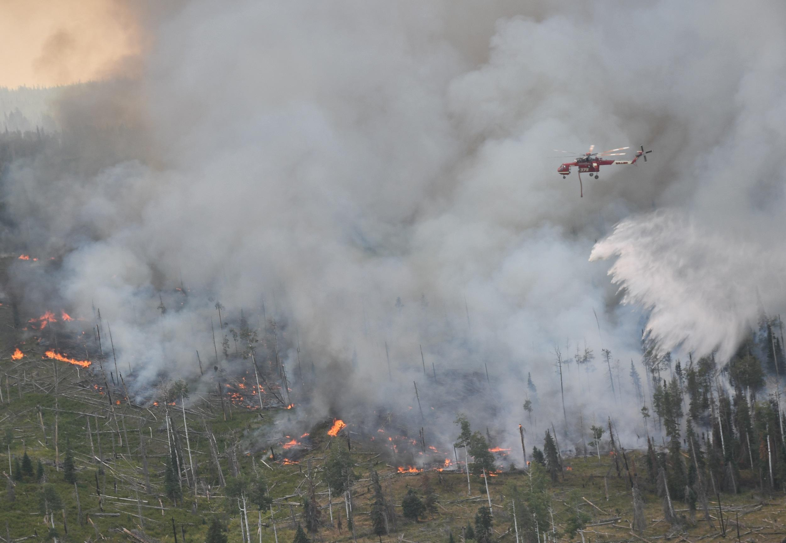 <p>A helicopter flies above the Cabin Lake Fire on Aug. 12, 2018.</p>