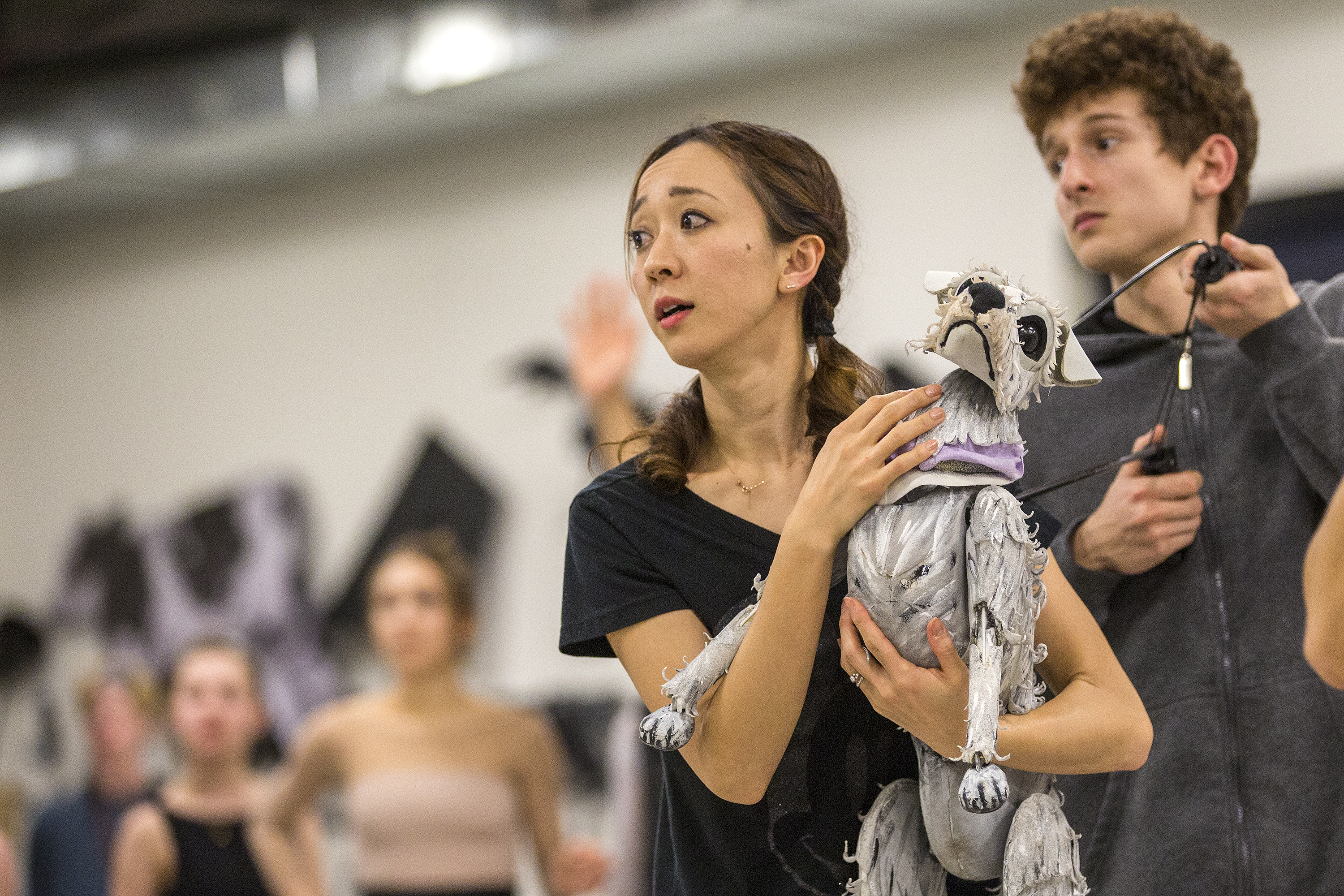 <p>Colorado Ballet dancer Asuka Sasaki and Toto puppeteer Benjamin Rose, with artists of Colorado Ballet in the background, in rehearsal on Jan. 25, 2019.</p>