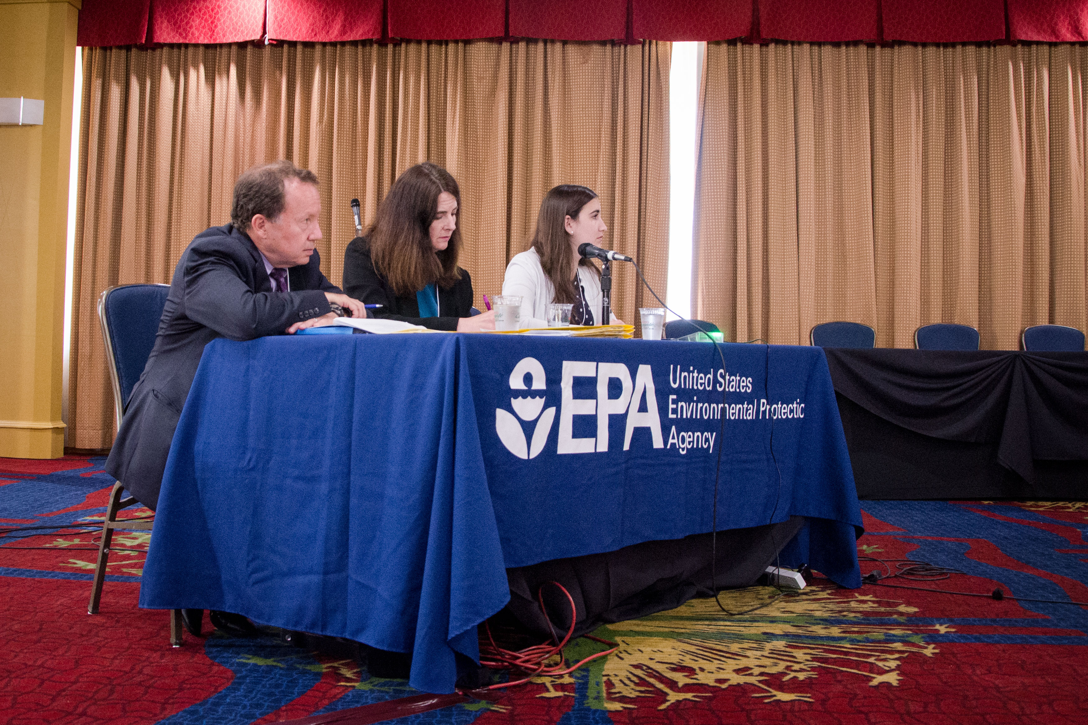 <p>Doug Benevento, regional administrator for EPA's Mountains & Plains Region 8, left, and staff listen to speakers during a PFCscommunity engagement event in Colorado Springs.</p>
