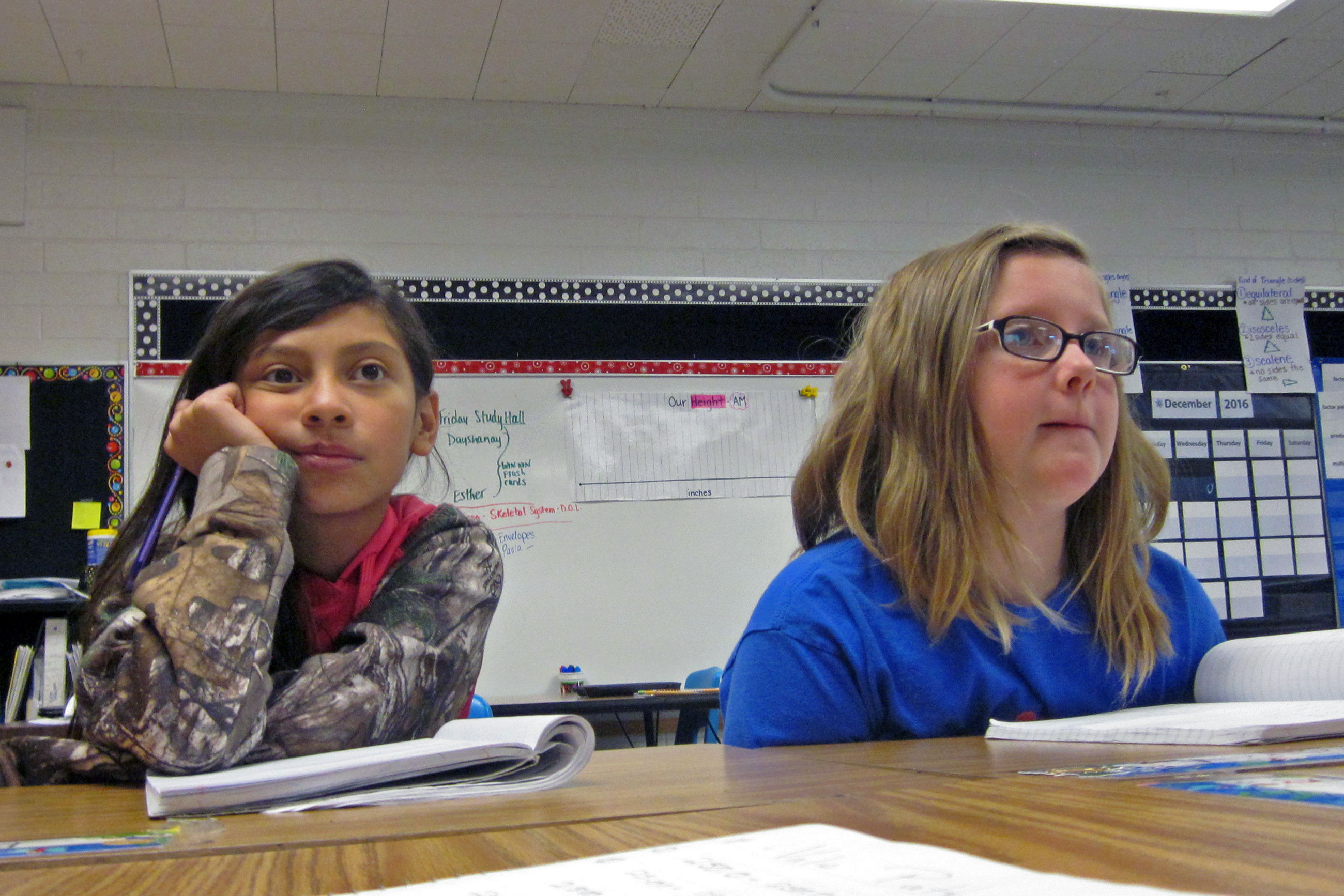 <p>Paola Flores and Cadence Johnson pay attention during a fifth grade math class where they often work in small groups because there are two teachers in class.</p>