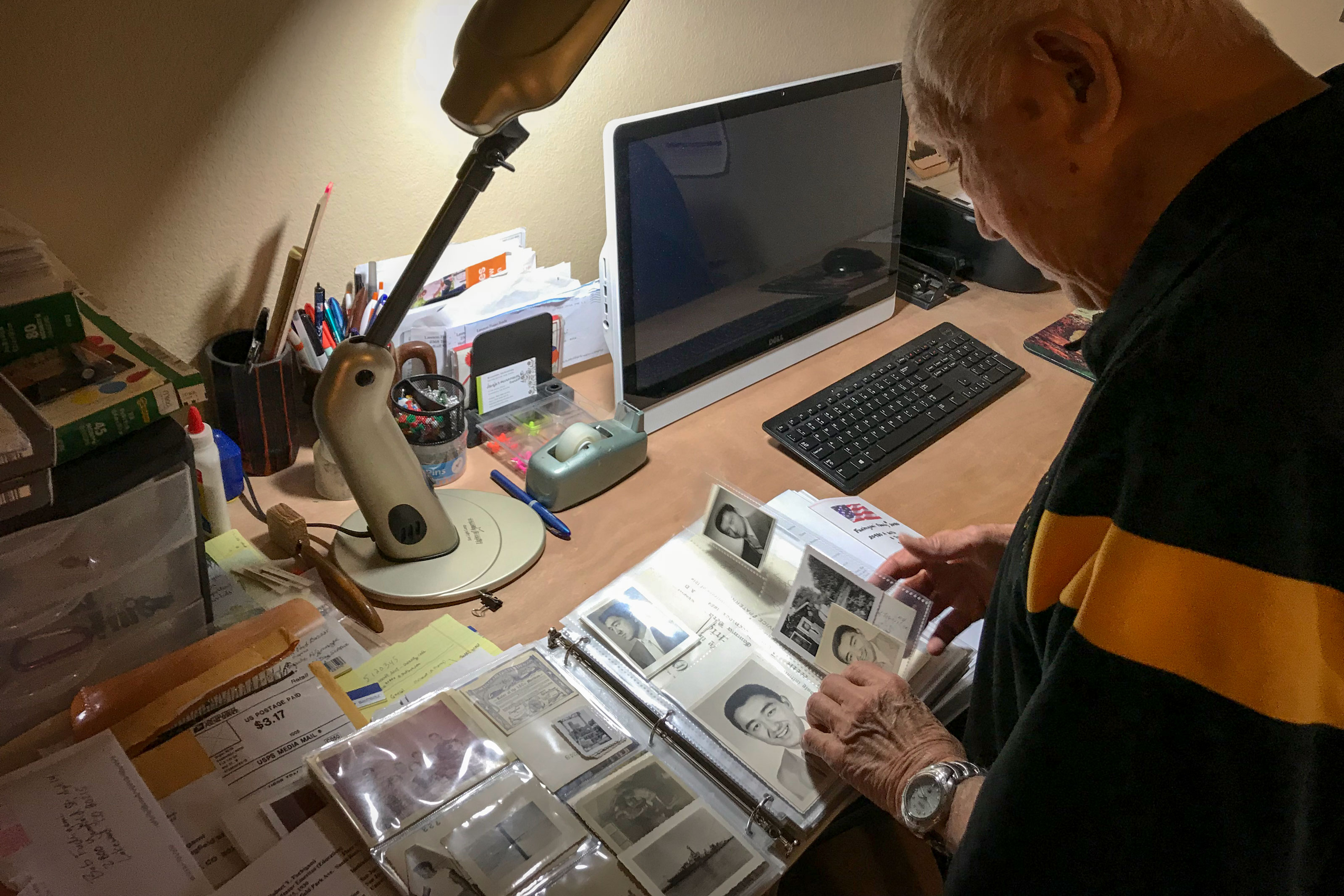 <p>88-year-old Bob Fuchigami looks through a binder of family photos at his home in Lakewood. He spent more than 3 years without freedom as an incarcerated Japanese-American during World War II.</p>