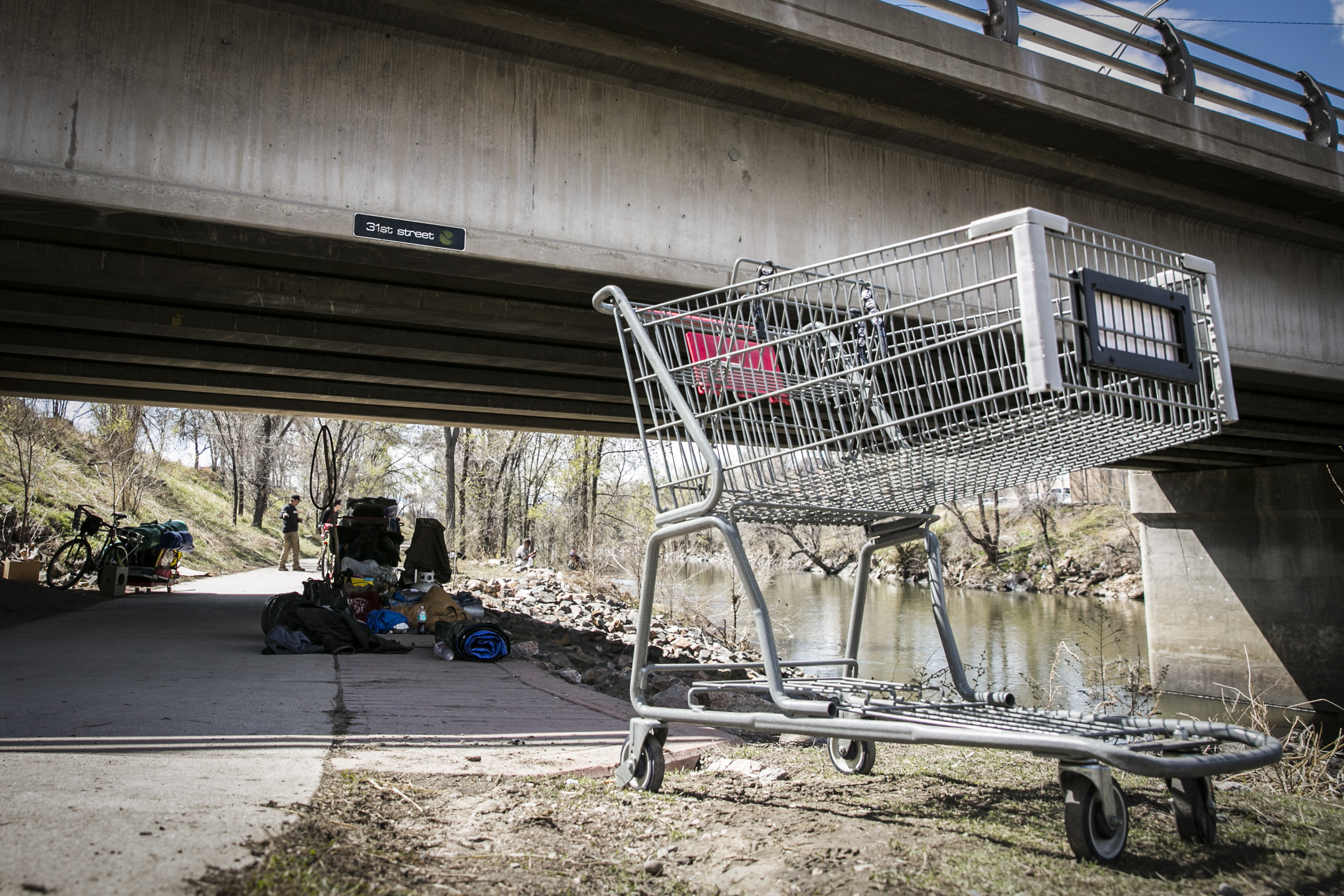 A shopping cart rests near a temporary homeless camp bythe 31st Street Bridge near the South Platte River outside of downtown Denver on Friday, April 1, 2016.