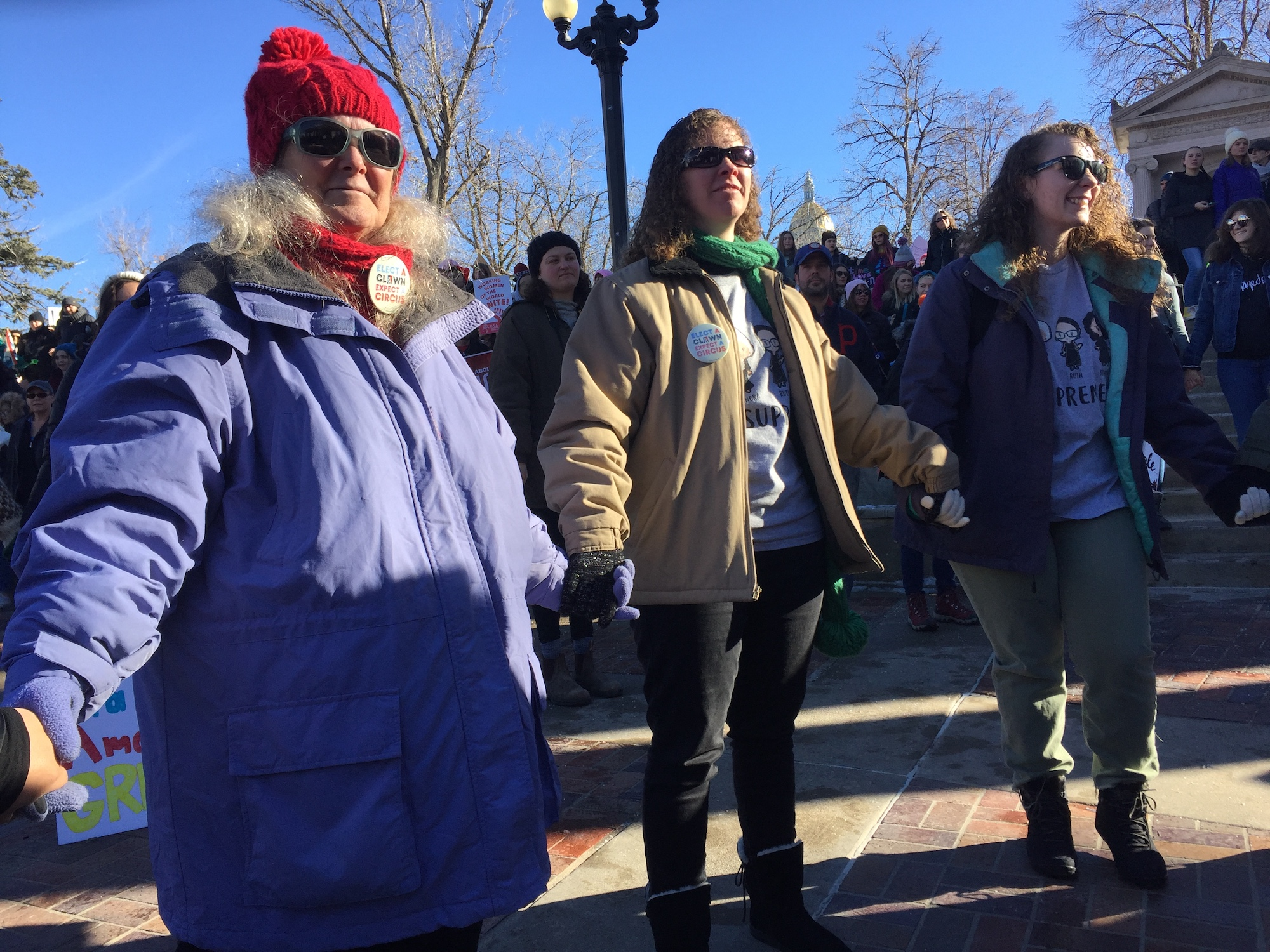 """<p>Three women hold hands at<span style=""""color: rgb(64, 69, 64);"""">the</span>Womxn's<span style=""""color: rgb(64, 69, 64);"""">March Denver on Jan. 19, 2019 in Civic Center Park in Denver</span>to demonstrate the march's theme of unity. A march organizer had asked everyone to join hands with the people next to them.</p>"""