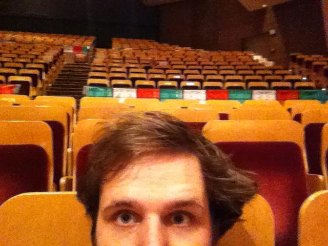 <p>Scott Carney in an empty Boettcher Concert Hall watching</p>