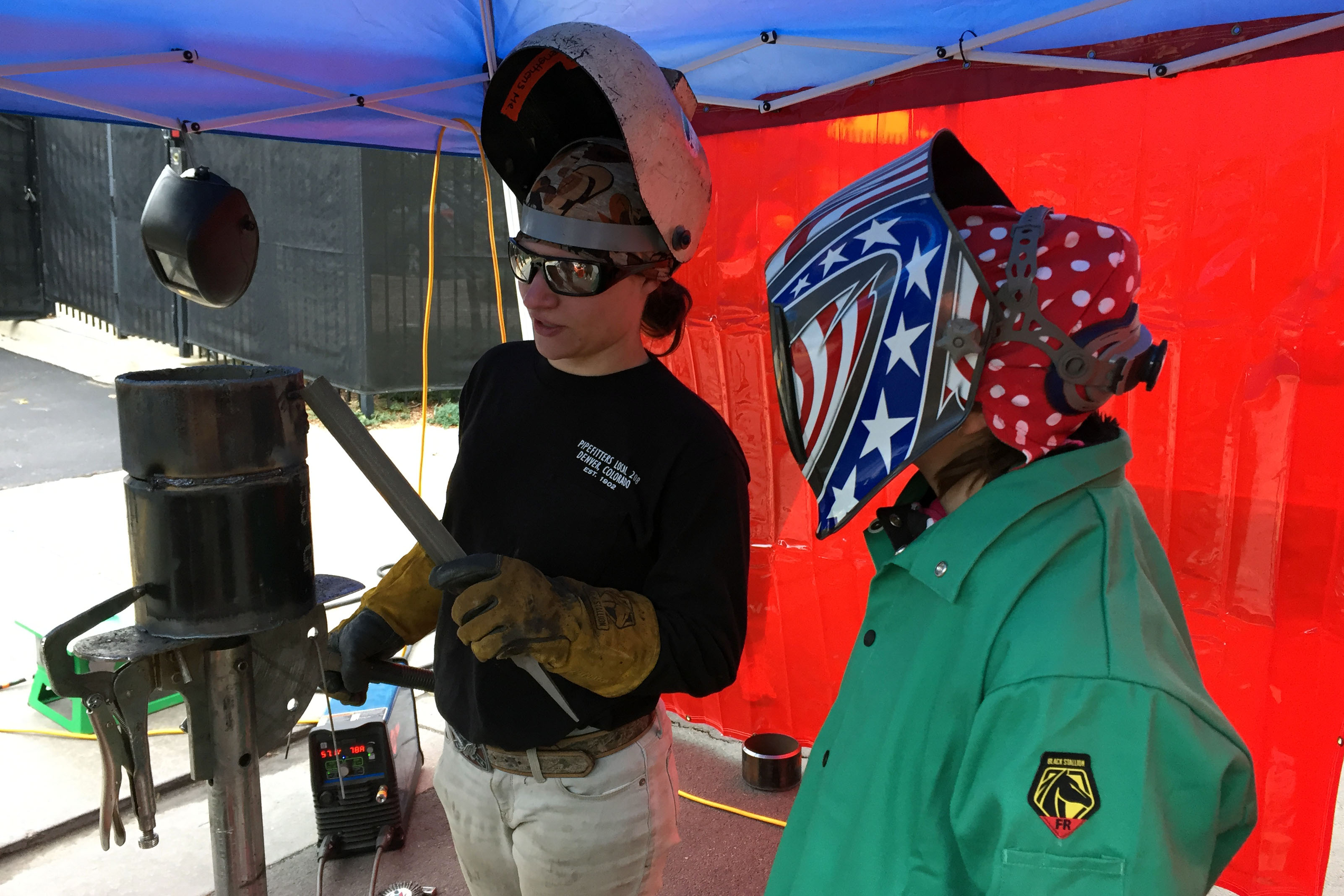 "<p>Rachel Neeb (left), a second-year pipefitting apprentice, shows 12-year-old Rayna Jeannelle (right) how to weld. The two were attending the Transportation and Construction Girl career fair at the <span style=""color: rgb(64, 69, 64);"">Renaissance Hotel Stapleton in Denver. The annual event exposes young girls and teenagers to jobs in male-dominated fields.</span></p>"