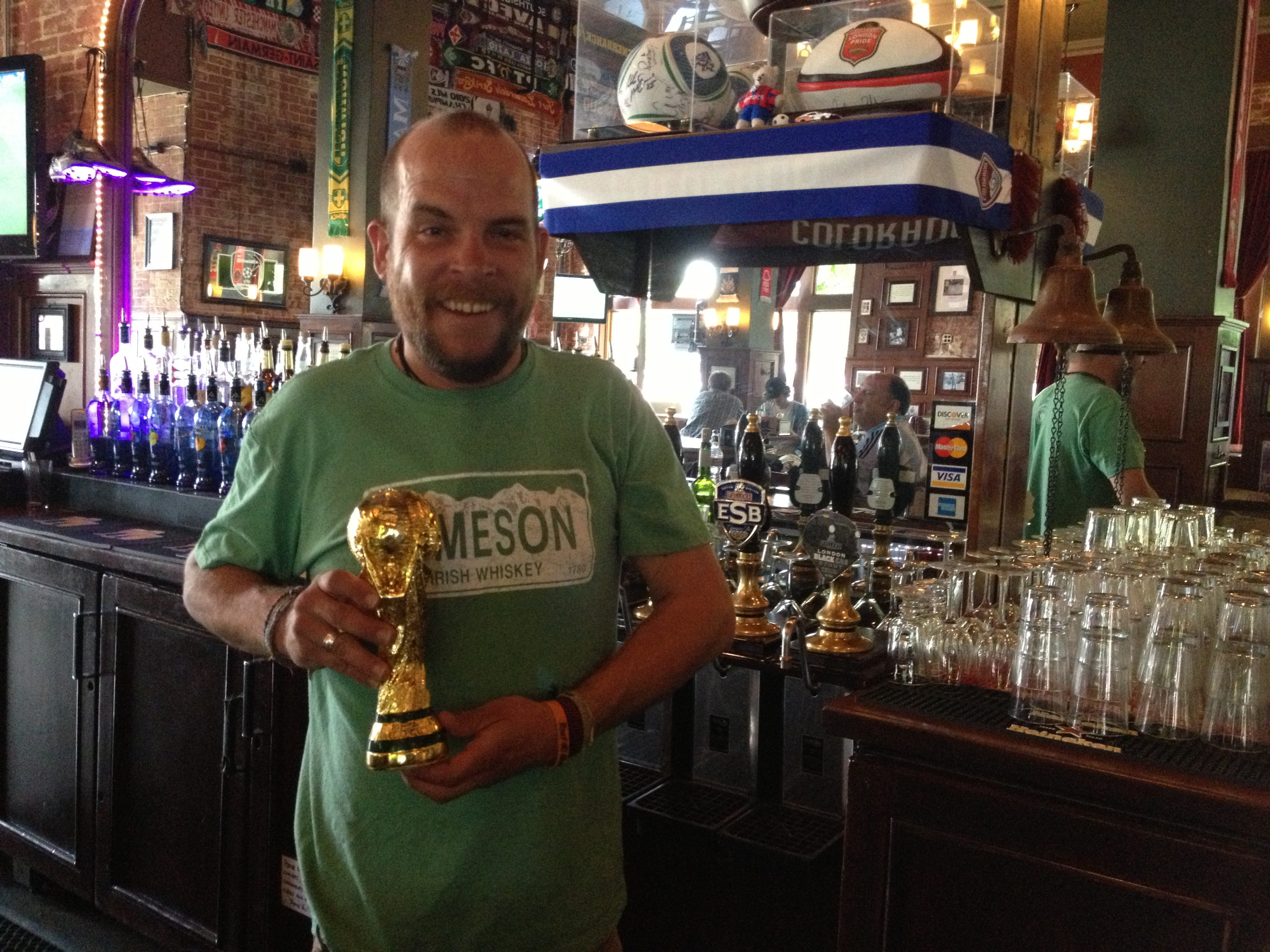 <p>Bartender Jeremy Allen at Denver's Three Lions pub holds a replica of the World Cup trophy.</p>