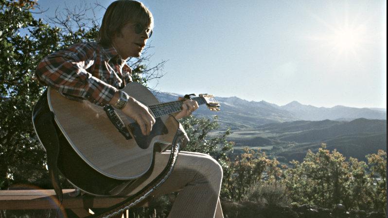 <p>John Denver with his guitar.</p>