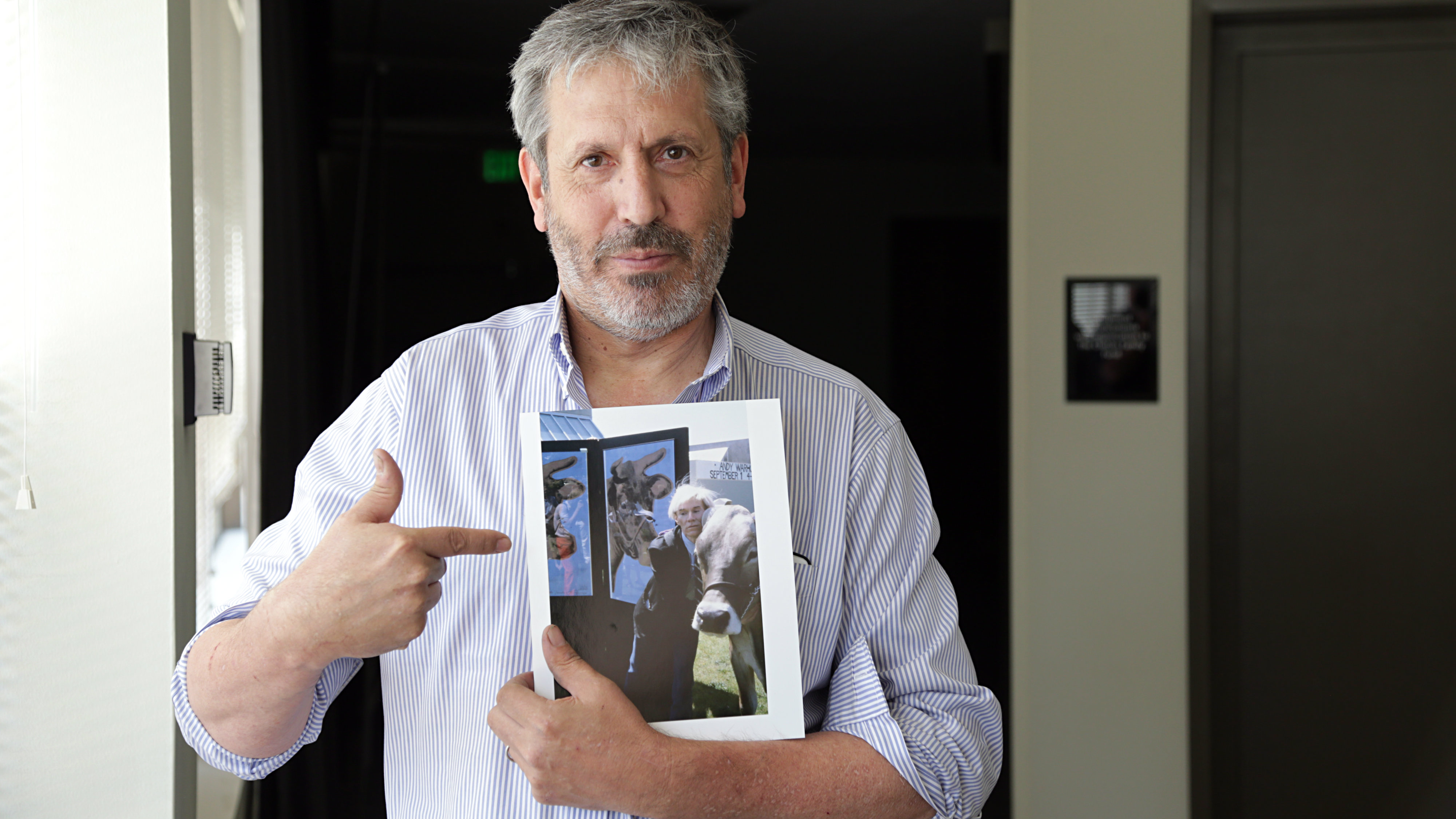 <p>Denver photographer Mark Sink holds an image he took of Andy Warhol during one of the pop artist's visits to Colorado.</p>