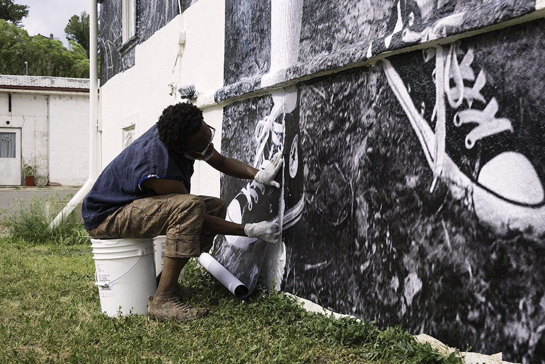 <p>Chip Thomas installs a mural photo outside the Church of Art in Hotchkiss, Colo.</p>