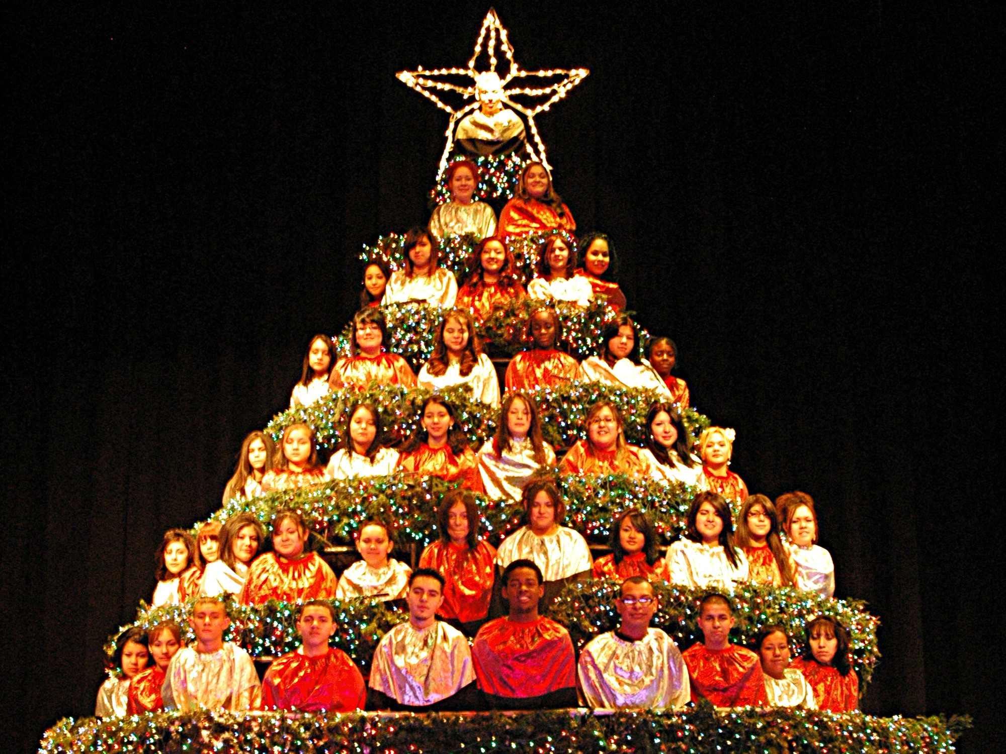 <p>West High students and alumni accompanied by a three-piece band sing holiday tunes amid the boughs of a fifteen-foot steel frame Christmas tree.</p>