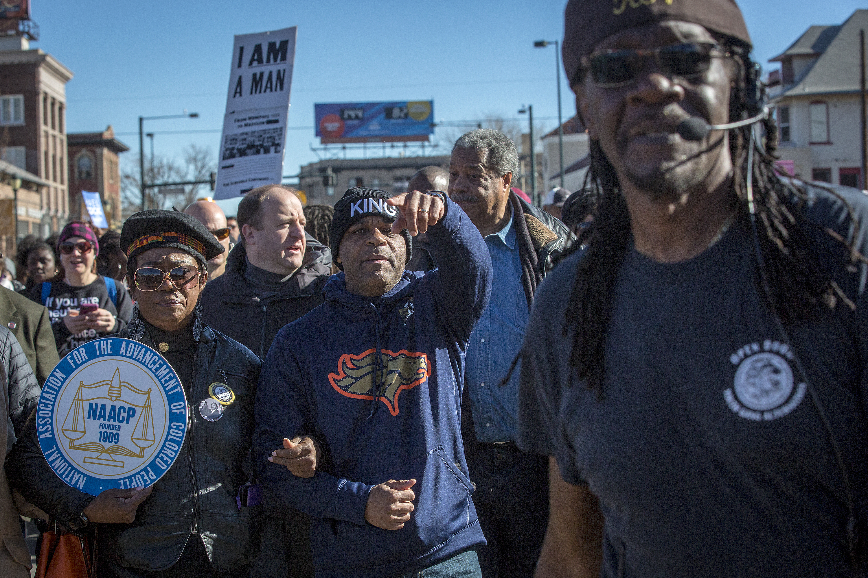 <p>Gov. Jared Polis, Denver Mayor Michael Hancock and former Mayor Wellington Webb march in the 2019 Marade on Denver's Colfax Avenue on Monday Jan. 21, 2019. The Rev. Leon Kelly, with microphone, is at right.</p>