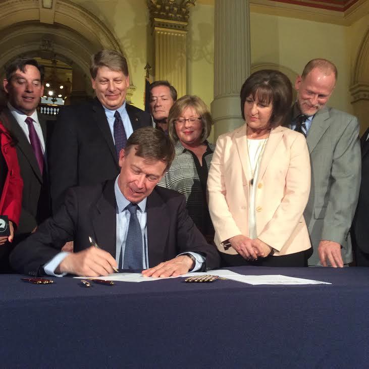<p>State legislators, along withDesiree and Michael Davis,watch as Gov. Hickenlooper signs school safety bills.</p>