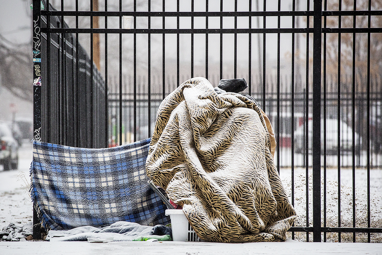 <p>Covered by a blanket and snow, a person sat near a streetcorner in Denver's Ballpark neighborhood Wednesday morning Feb. 6 2019.</p>