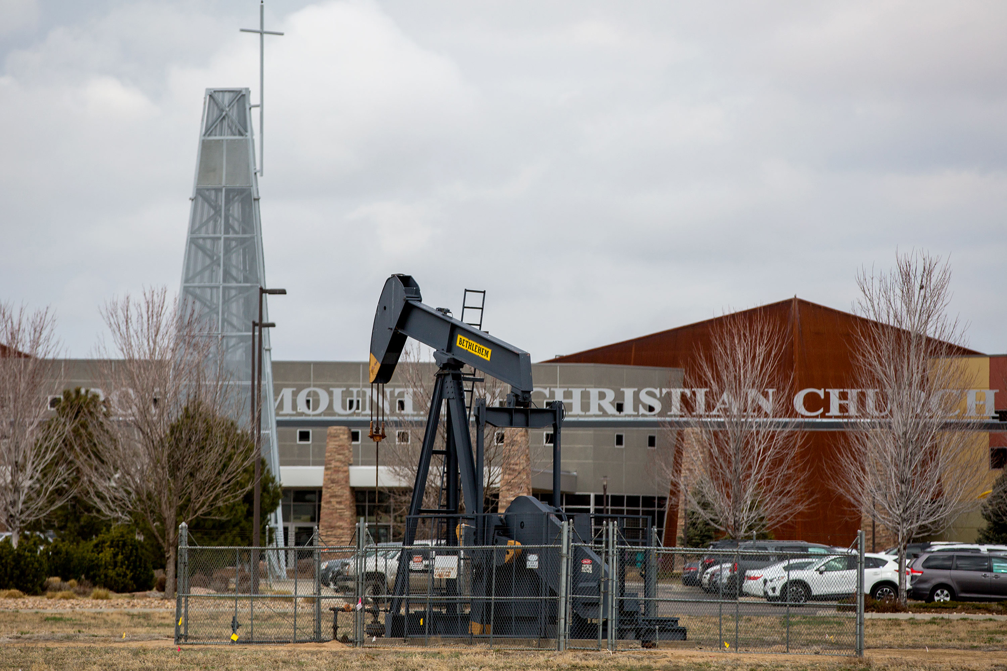 A pump jack that feeds storage tanks beside the parking lot of Rocky Mountain Christian Church in Firestone, April 2, 2019.
