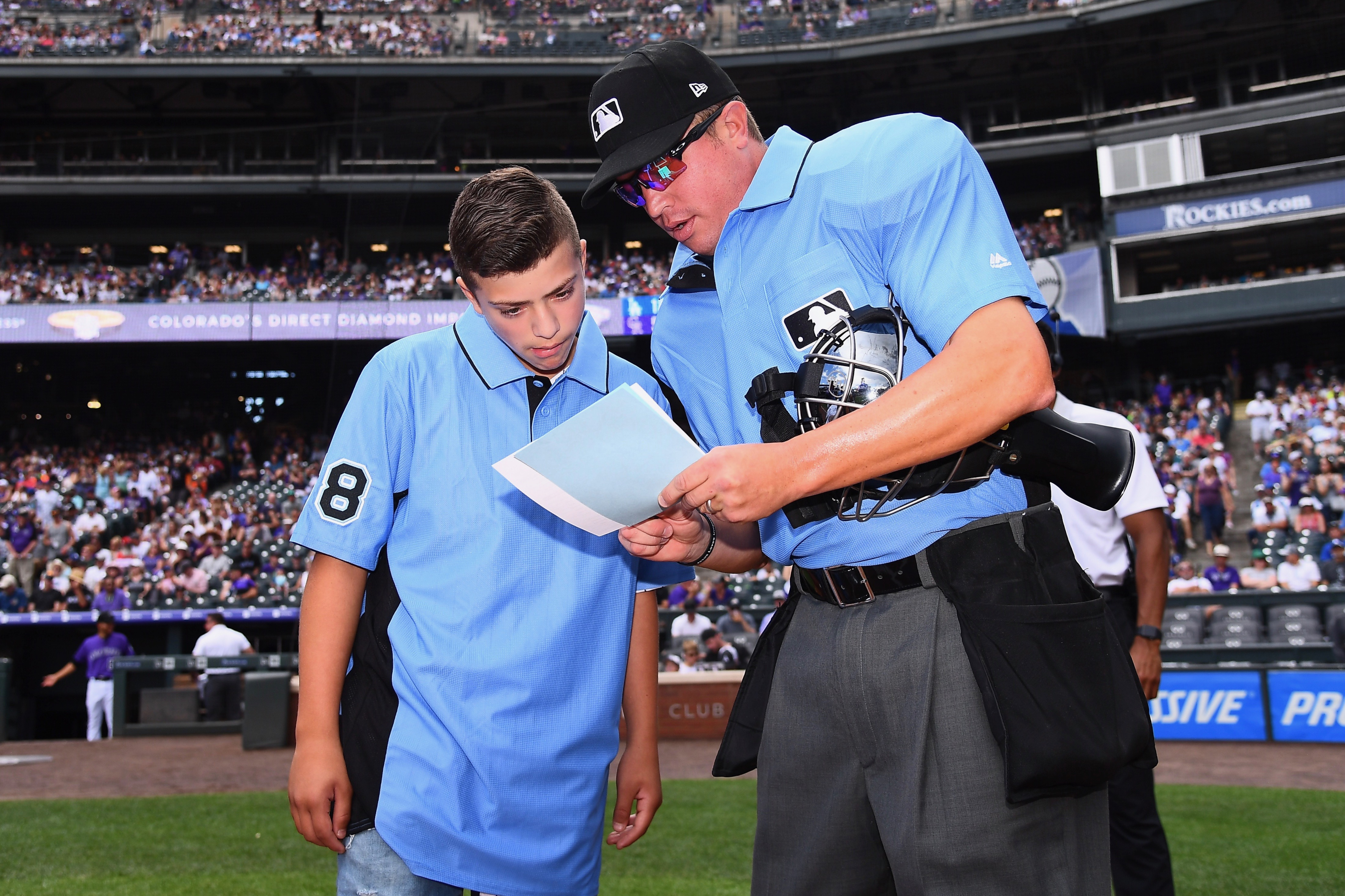 Josh Cordova, 13, gets pre-game instructions from umpire Cory Blaser before theRockies-Dodgers game at Coors Field on Sunday, June 30, 2019. Cordova was the umpire at a youth game last month in Lakewood that ended in a brawl among parents and coaches.