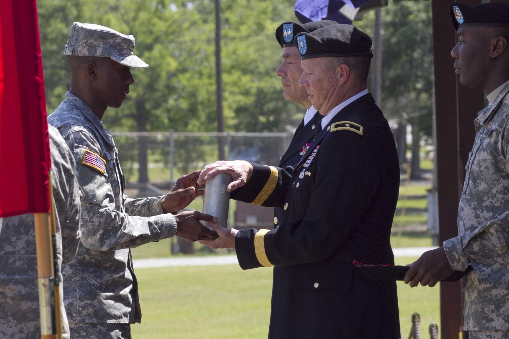 <p>Gen. William J. Gothard (right) receives a spent shell casing as part of his 2014 retirement ceremony at Fort Jackson, S.C. Gothard says his 36 years of service left him with hearing loss and tinnitus.</p>