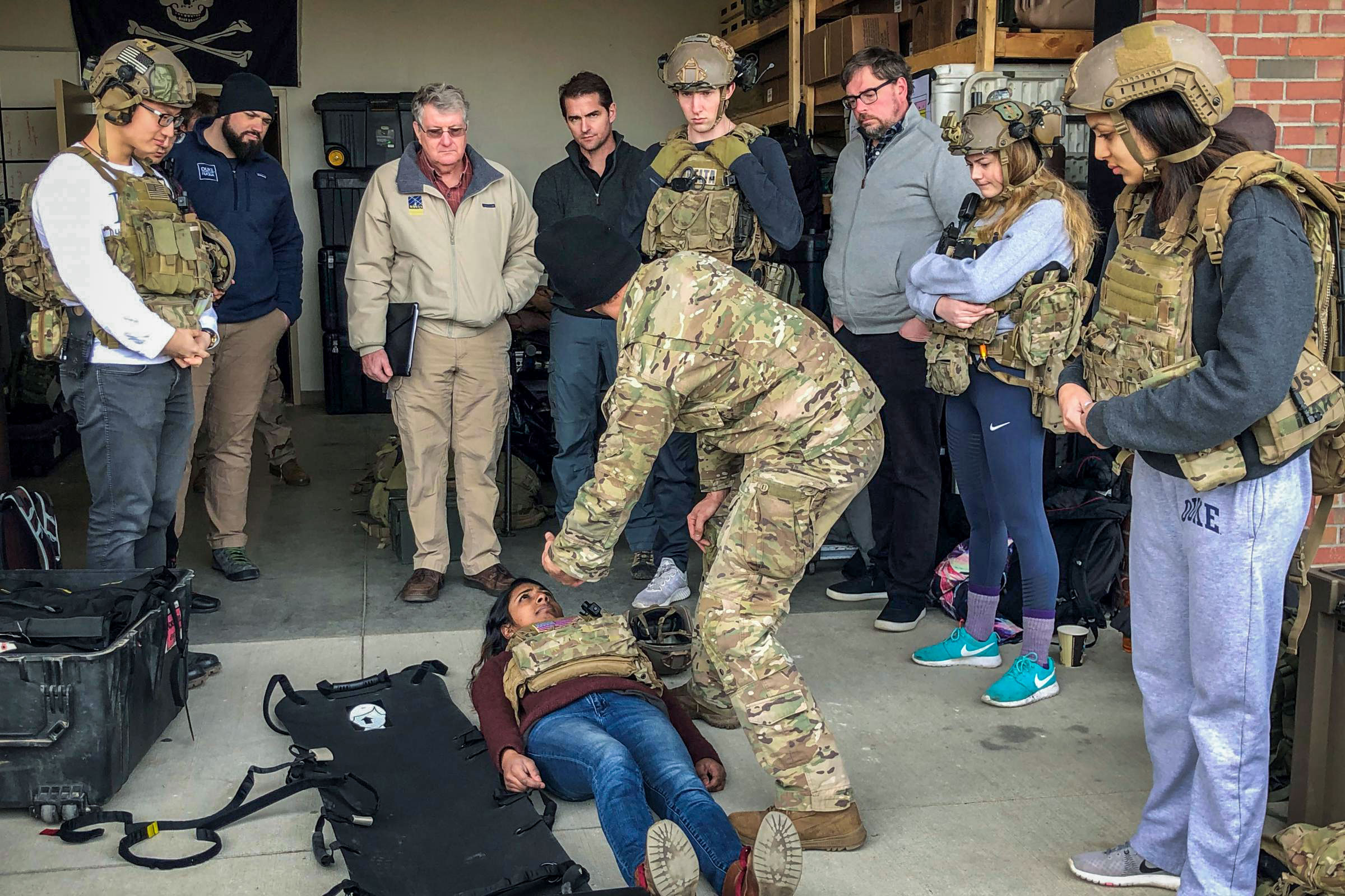 <p>Using a student as a simulated casualty, an Army medic at Fort Bragg explains his work to a Duke University class.<br />