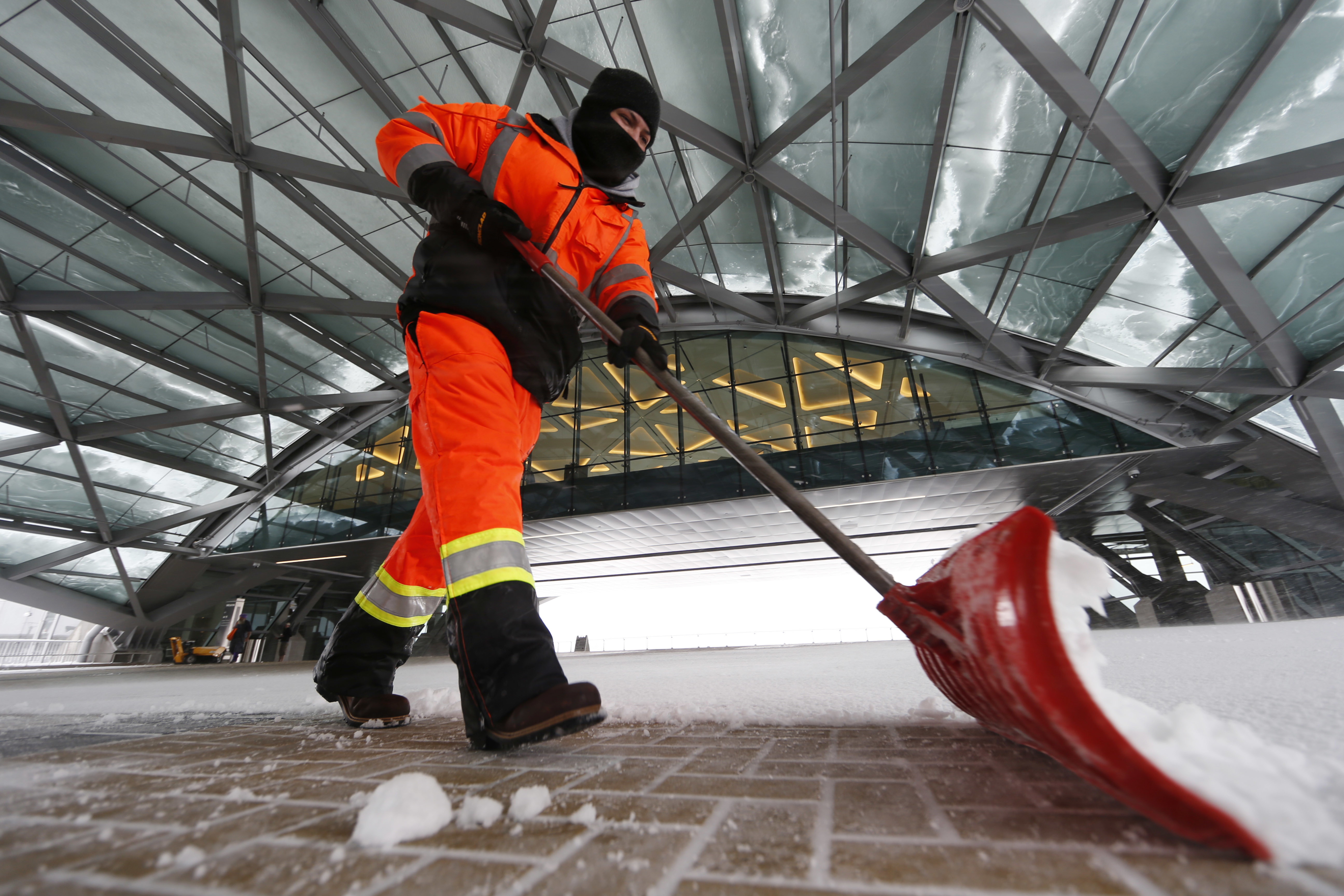<p>Joseph Dominguez uses a shovel to clear snow between the main terminal of Denver International Airport and the adjoining hotel Saturday, April 16, 2016, in Denver.</p>