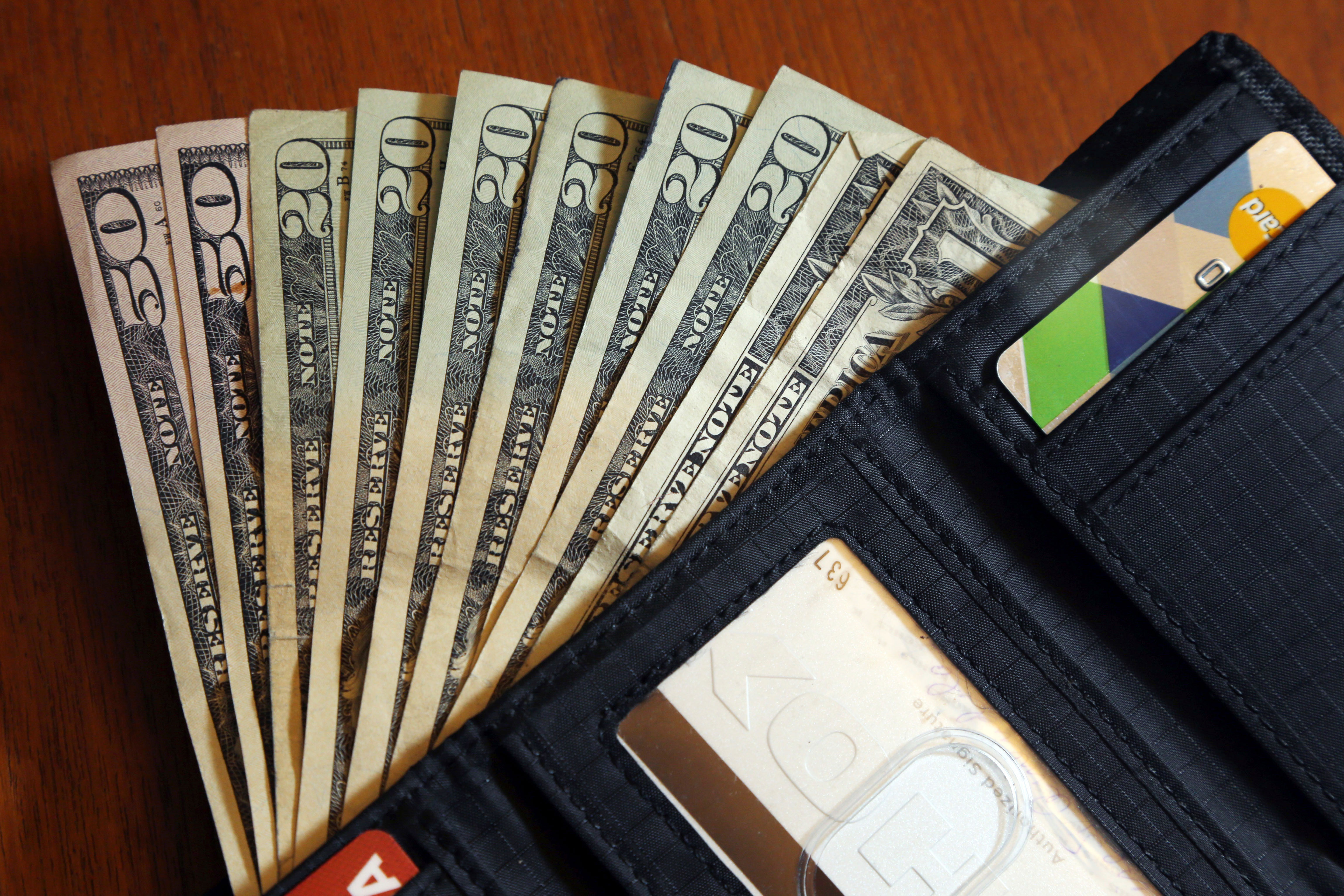 <p>Cash fanned out from a wallet.</p>