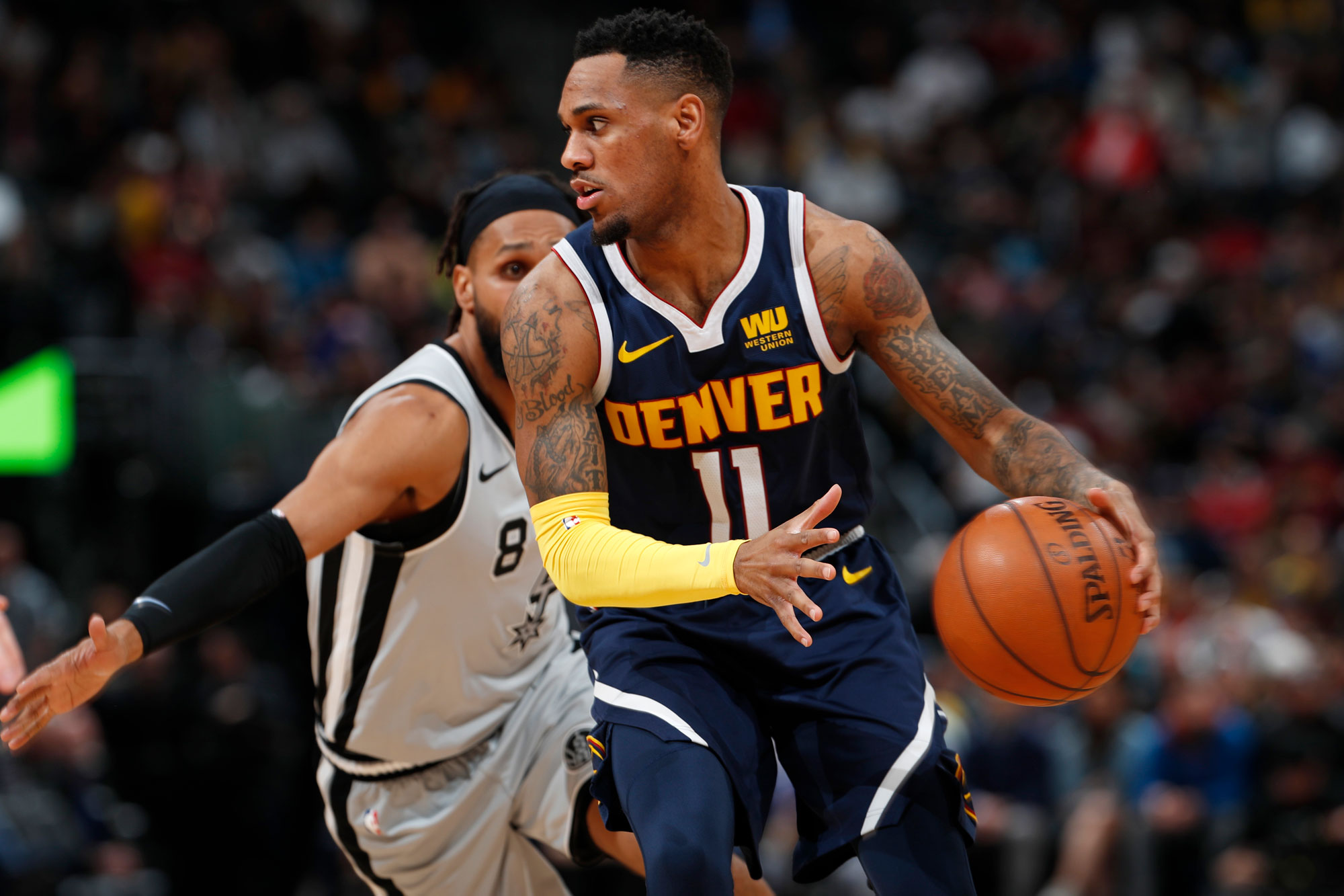 <p>Denver Nuggets guard Monte Morris, front, looks to pass the ball as San Antonio Spurs guard Patty Mills defends during the second half of an NBA basketball game Wednesday, April 3, 2019, in Denver. The Nuggets won 113-85.</p>
