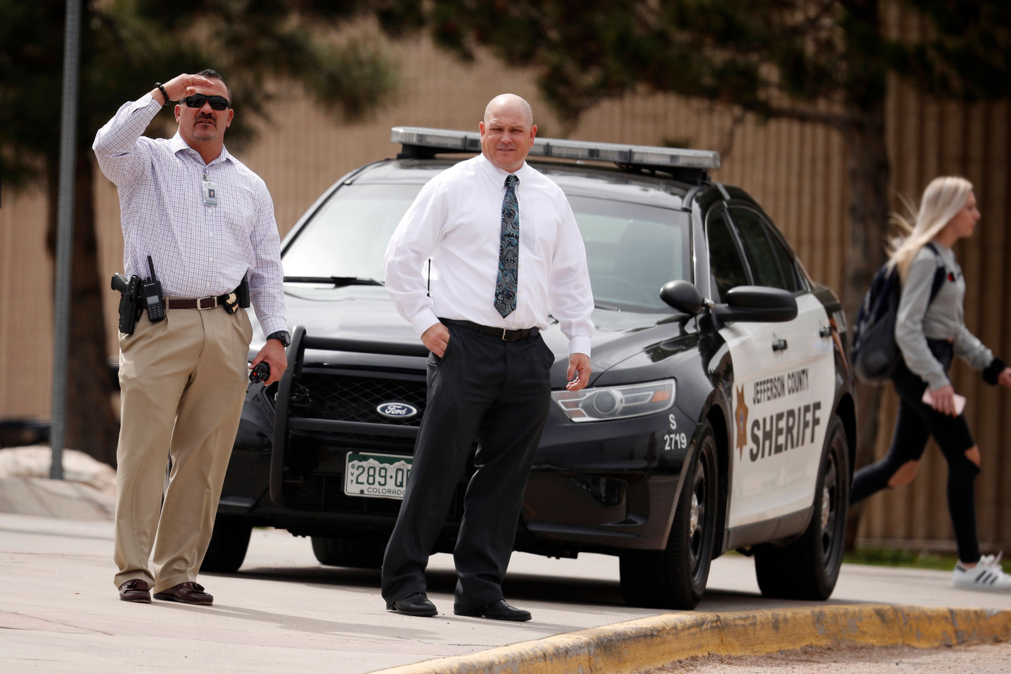 <p>Columbine High School principal Scott Christy, right, joins an officer in watching as students leave the school late Tuesday, April 16, 2019, in Littleton, Colo. Following a lockoutat Columbine High School and other Denver area schools, authorities say they are looking for a woman suspected of making threats.</p>
