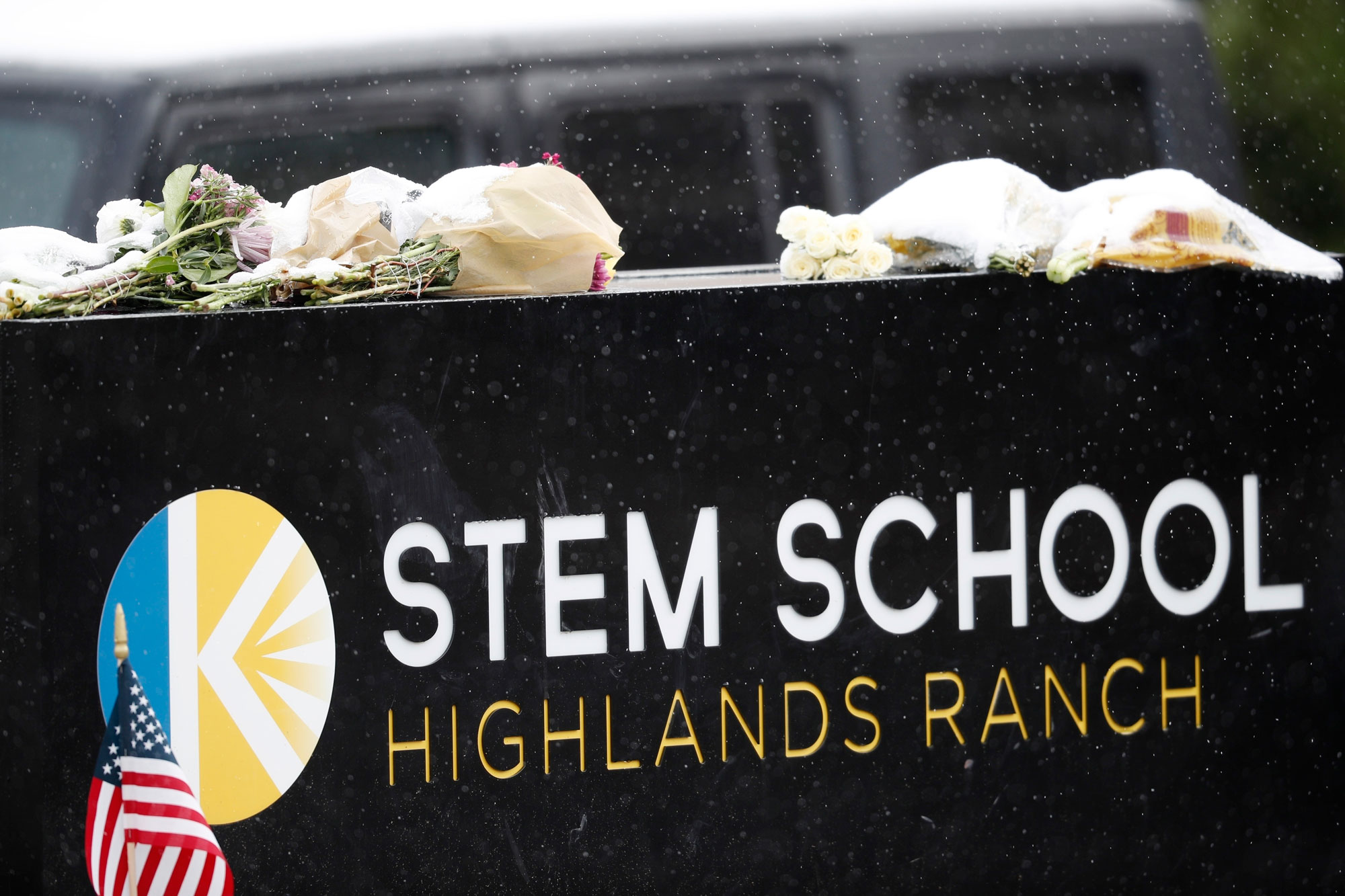 A light snow covers bouquets of flowers placed on the sign for STEM School Highlands Ranch following Tuesday's shooting, in Highlands Ranch, Colo., Thursday, May 9, 2019.