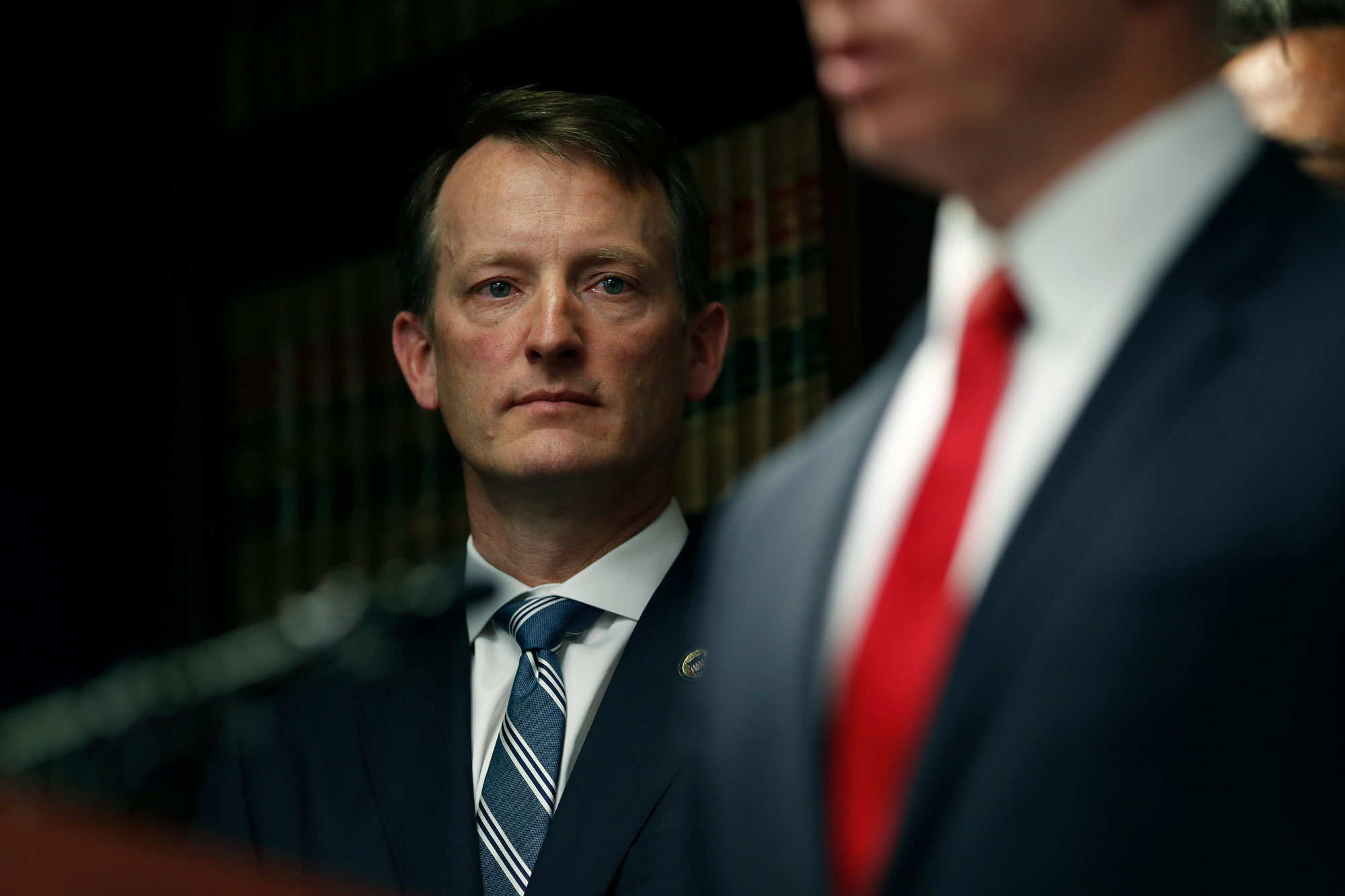 <p>U.S. Attorney Jason Dunn, left, listens as George Brauchler speaks during a news conference to announce the arrest of 42 people this week in one of the largest black market marijuana enforcement actions in the history of Colorado Friday, May 24, 2019, in Denver.</p>