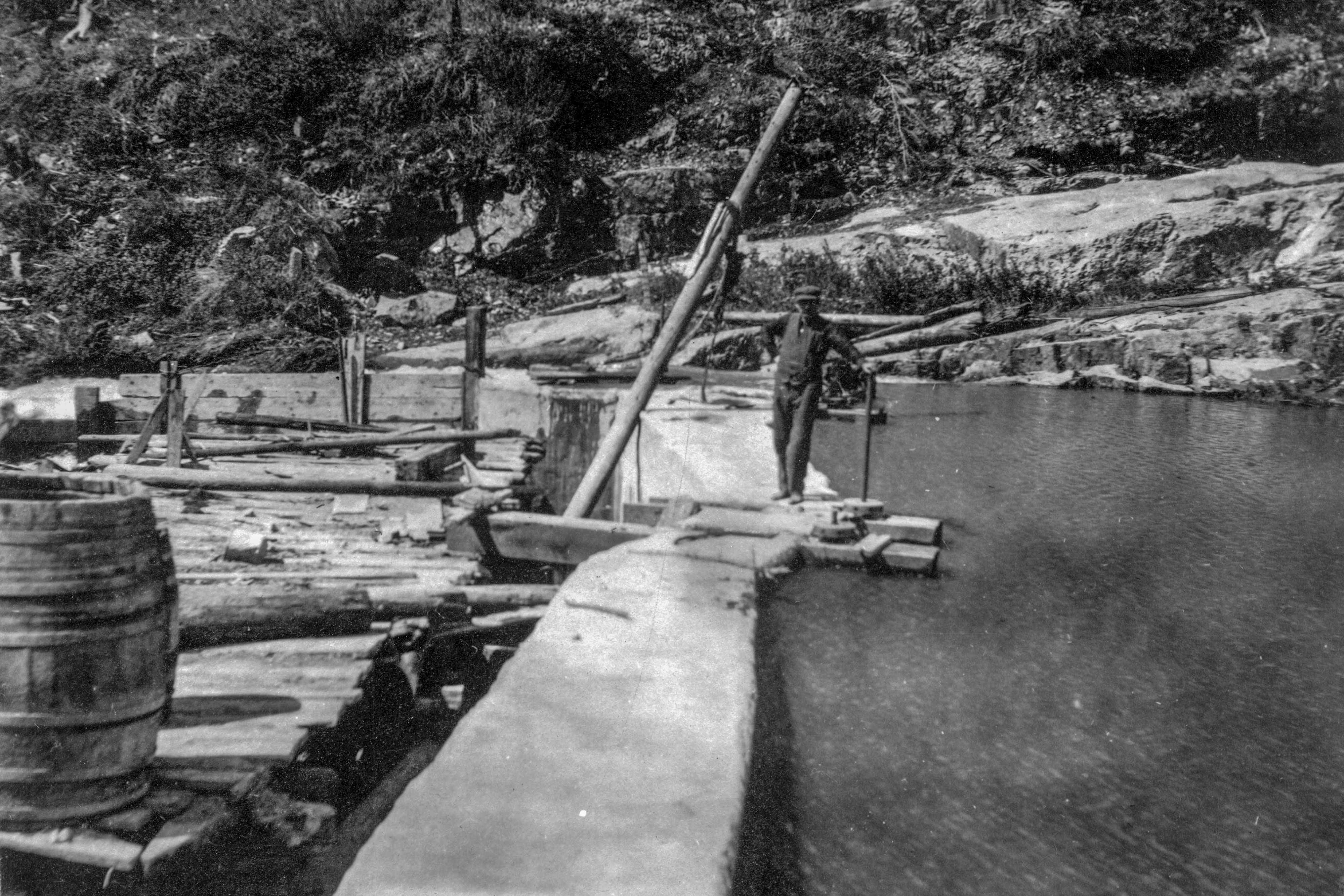 <p>A man poses by the spillway of the Hidden Treasure Dam which is adjacent to the Hidden Treasure Mine and Mill near Lake City, Hinsdale County, Colo., sometime between 1920-1930.</p>