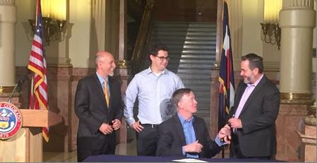 <p>Colo. Governor John Hickenlooper signs a bill at theState Capitol in Denverasking voters to allow the state to keep revenue generated from marijuana sales.</p>