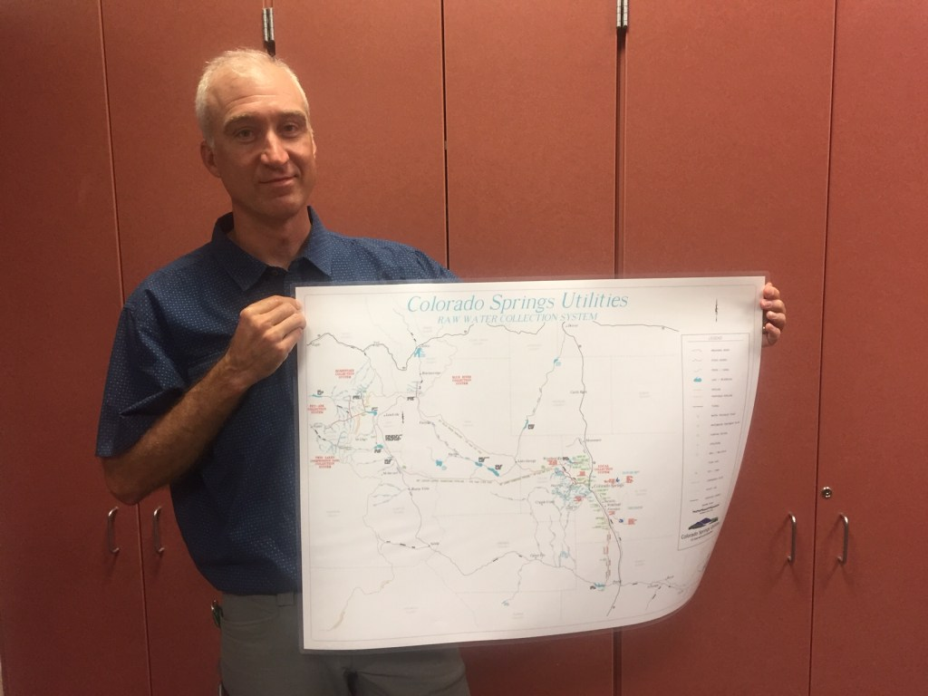 Mark Shea with Colorado Springs Utilities holds up a map of water sources and infrastructure for the region.