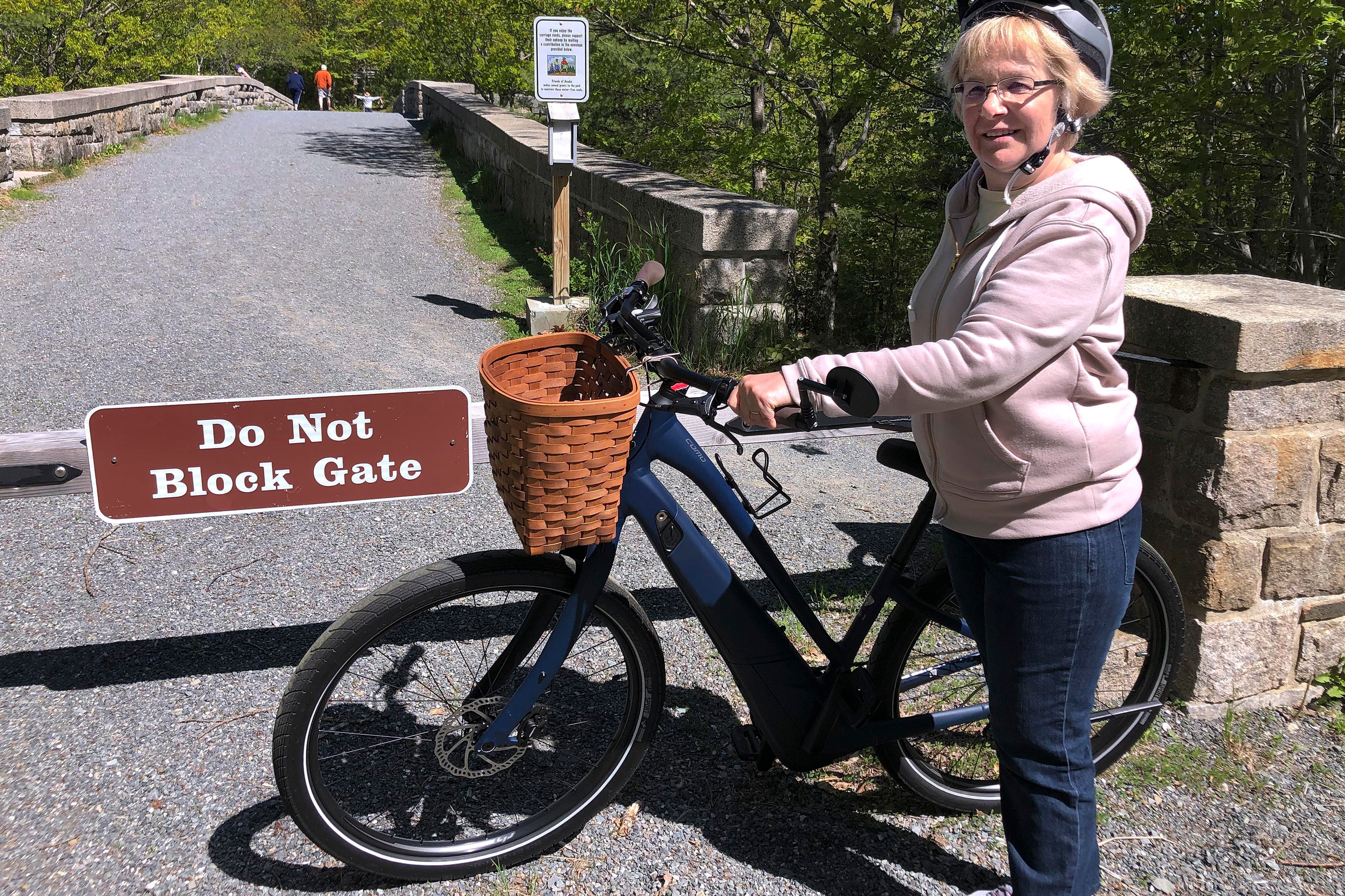 Janice Goodwin stands by her electric-assist bicycle at a gate near the start of the carriage path system where bikes such as her are banned inside Acadia National Park, in this photo June 8, 2018, in Bar Harbor, Maine. Electric-assist bikes are allowed on paved roads but are banned on bike paths in national parks.