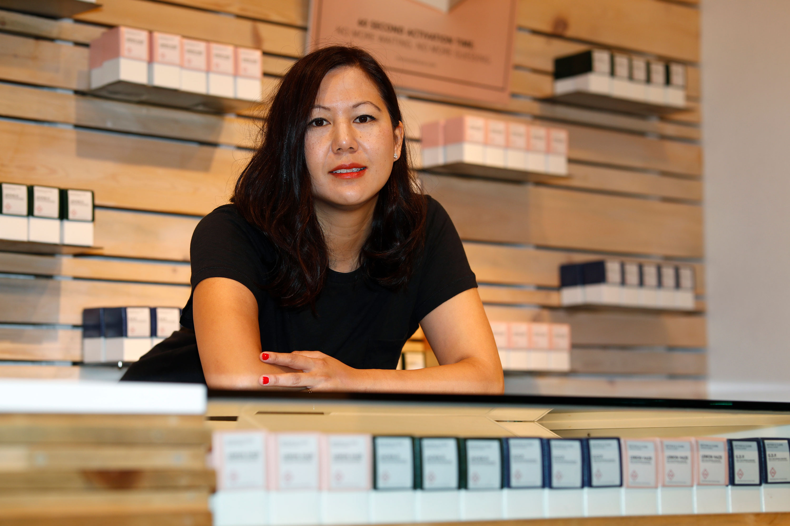"In this Friday, July 26, 2019 photo, Leslie Siu poses for a portrait next to her cannabis products geared toward women on display in Groundswell dispensary in east Denver. Pregnancy started out rough for her. Morning sickness and migraines had her reeling and barely able to function at a demanding New York marketing job, so like rising numbers of U.S. mothers-to-be, she turned to marijuana. ""l was finally able to get out from under my work desk,"" said Siu, who later started her own pot company and says her daughter, now 4, is thriving."