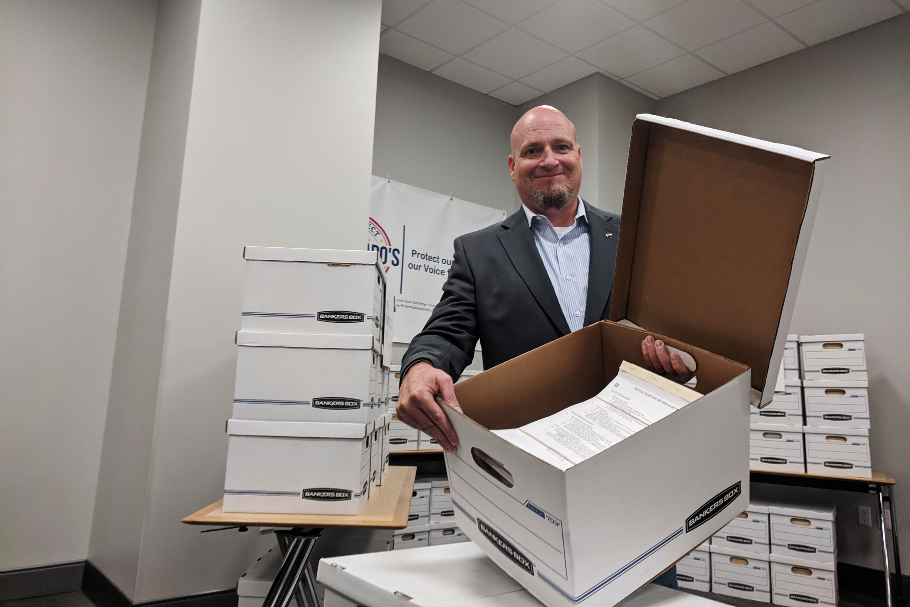 Monument Mayor Don Wilson, who's helping lead the repeal movement, delivers petitions to the Colorado Secretary of State on Thursday.