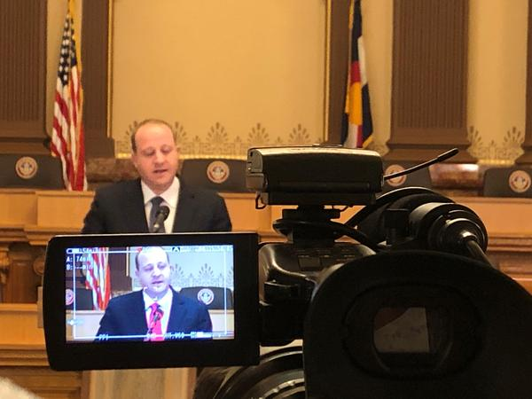 Gov. Jared Polis speaks during a press conference at the state Capitol in August.