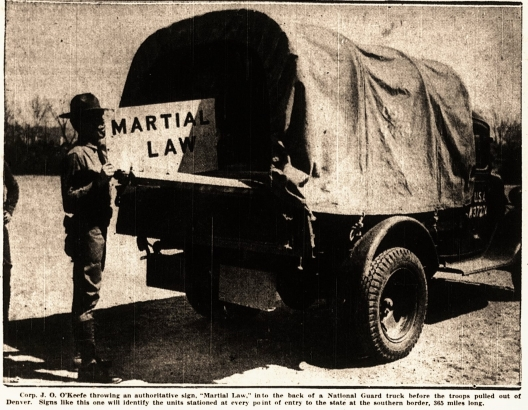 """A Denver Post clipping from April 20, 1936 shows a National Guardsman holding a sign that says """"Martial Law."""" The photo caption says that similar signs would mark troops stationed at southern points of entry into Colorado."""