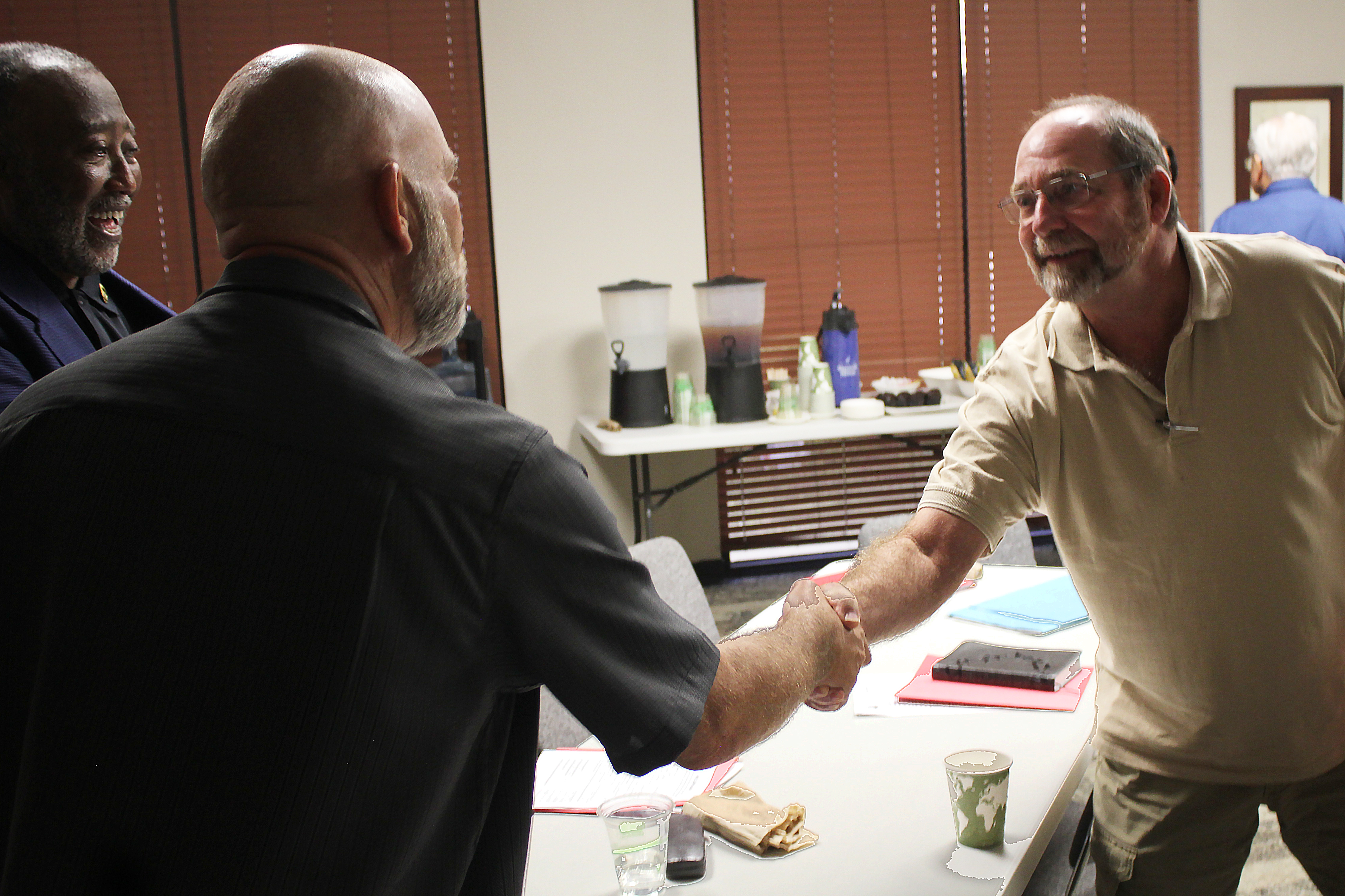 Mark George (right), a chaplain at the Caldwell County Jail in Lockhart, TX., shakes hands with VA clergy training instructor Larry Collins, while attendee Vernon Cooper looks on.