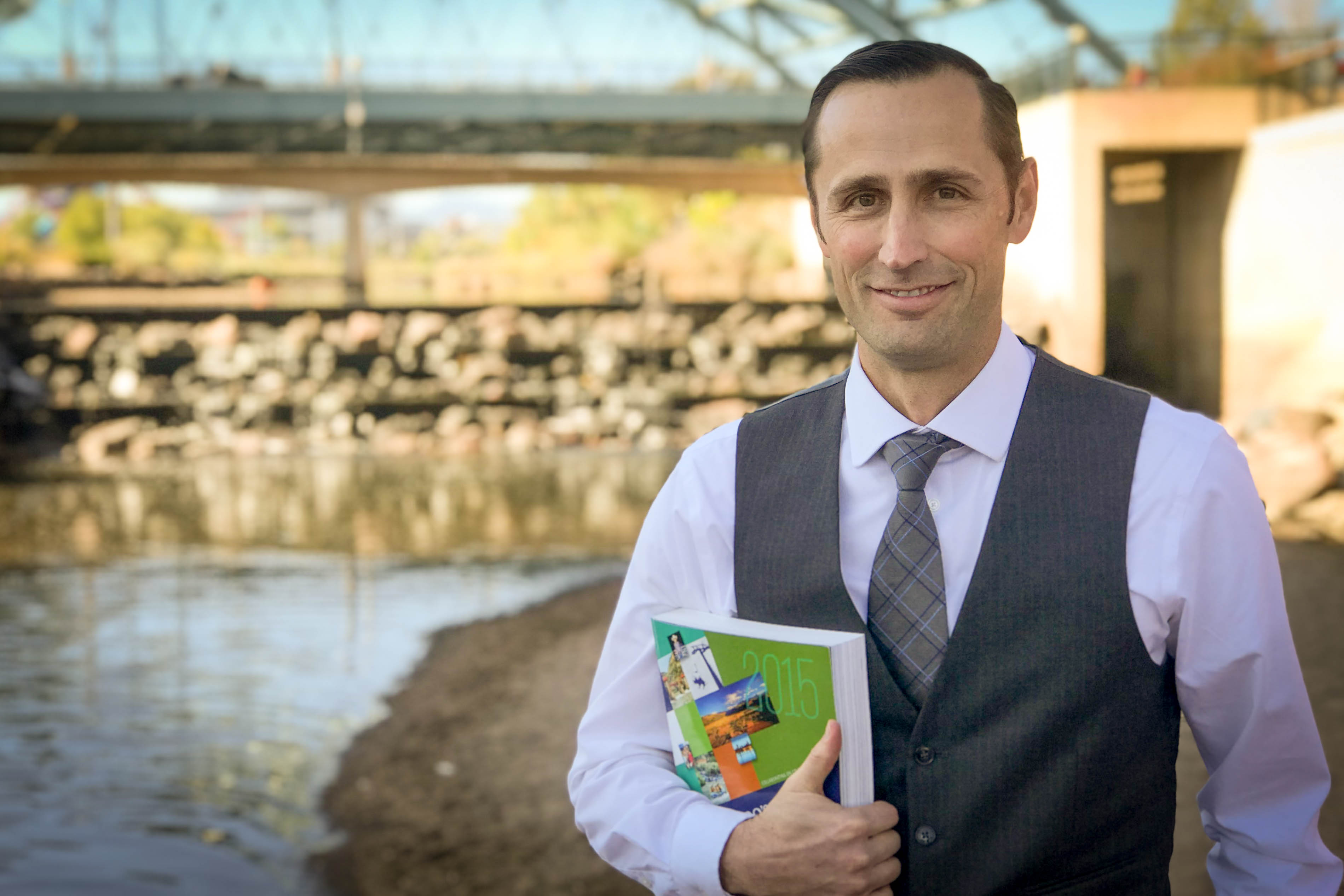 James Eklund, the architect of Colorado's Water Plan, holds a copy in front of the Platte River in Denver, Colo.