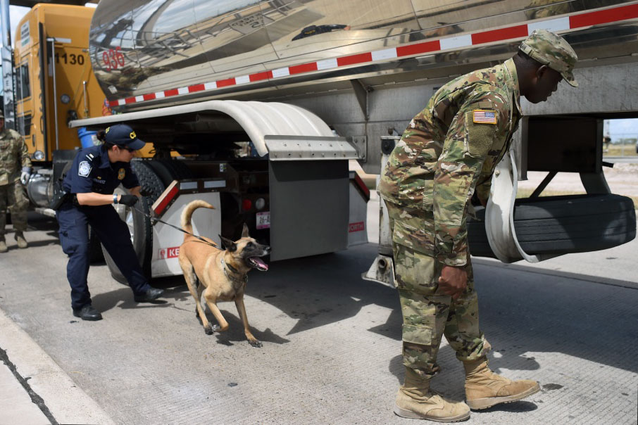 Spc. Afeez Amusan of the Texas Army National Guard, right, inspects a tractor-trailer alongside a U.S. Customs and Border Protection agent at the U.S.-Mexico border in Pharr, Texas.